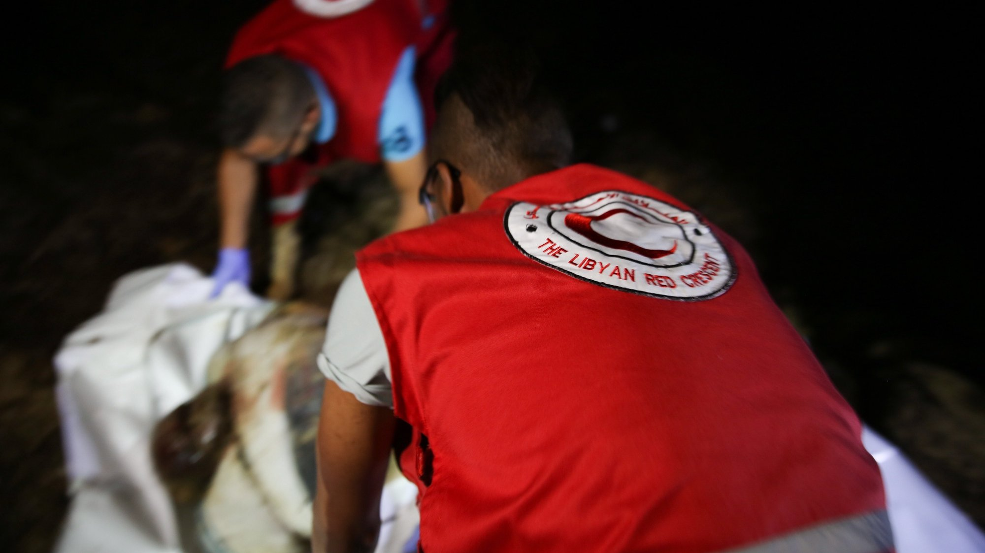 epa06860340 Libyan Red Crescent (LRC) rescue workers carry a body of a drowned migrant on a beach after being washed up, Tajoura, 14 kilometers east of Tripoli, Libya, 02 July 2018 (issued 03 July 2018). According to reports, Libyan rescuers found bodies of 17 drowned migrants over the past two days, after a migrant boat sank off the coast on 29 June with some 100 people missing in the incident.  EPA/STRINGER