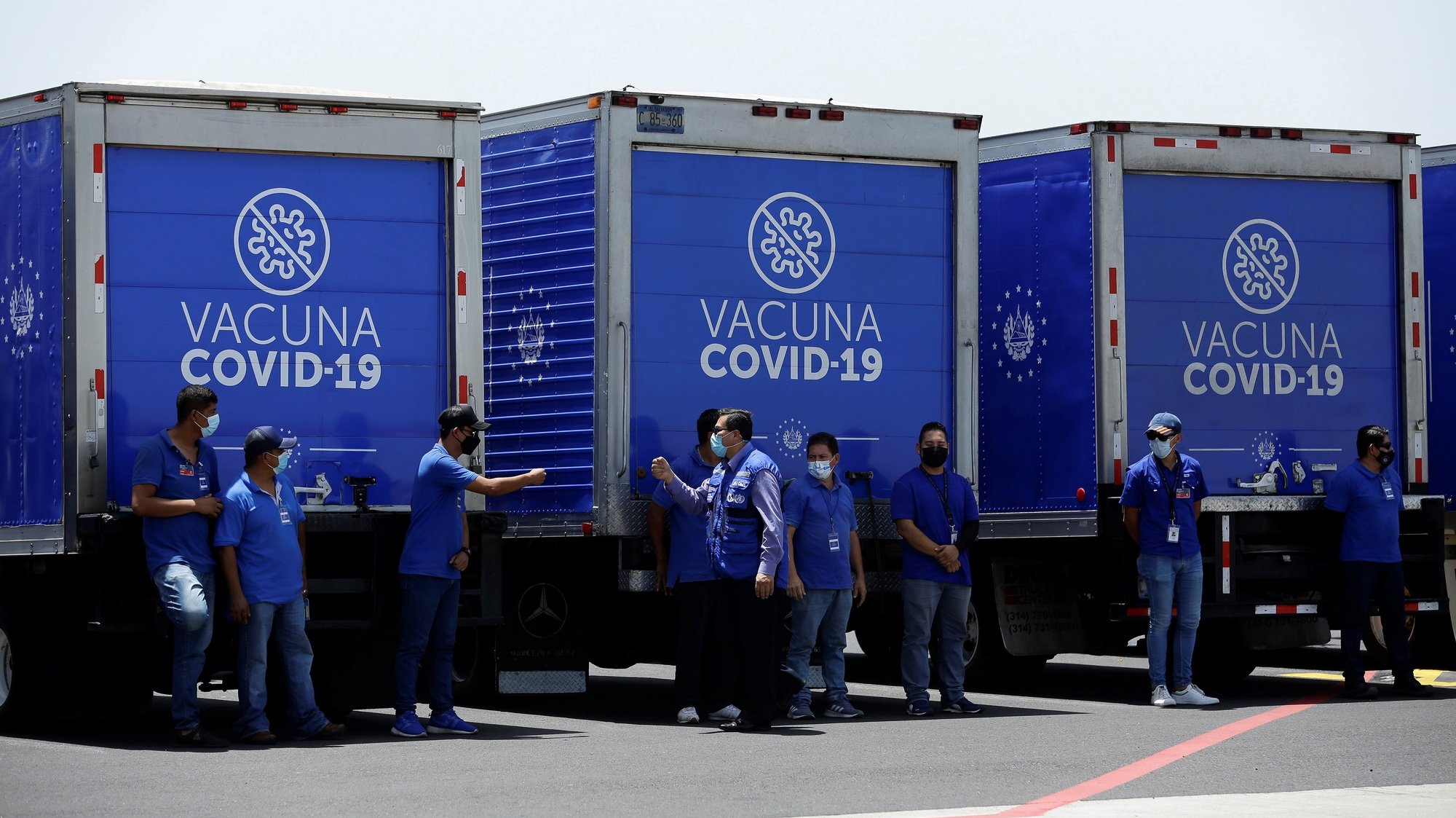 """epa09358764 View of health workers next to the refrigerated trucks that will transport a batch of vaccines, sent by the United States, against COVID-19, at the San Ã""""scar Romero International Airport in San Luis Talpa, El Salvador, 22 July 2021. The United States delivered a second batch of 1.5 million Modern vaccines against the SARS-CoV-2 coronavirus to El Salvador on Thursday, as part of a donation through the Covax system of the World Health Organization (WHO).  EPA/Rodrigo Sura"""