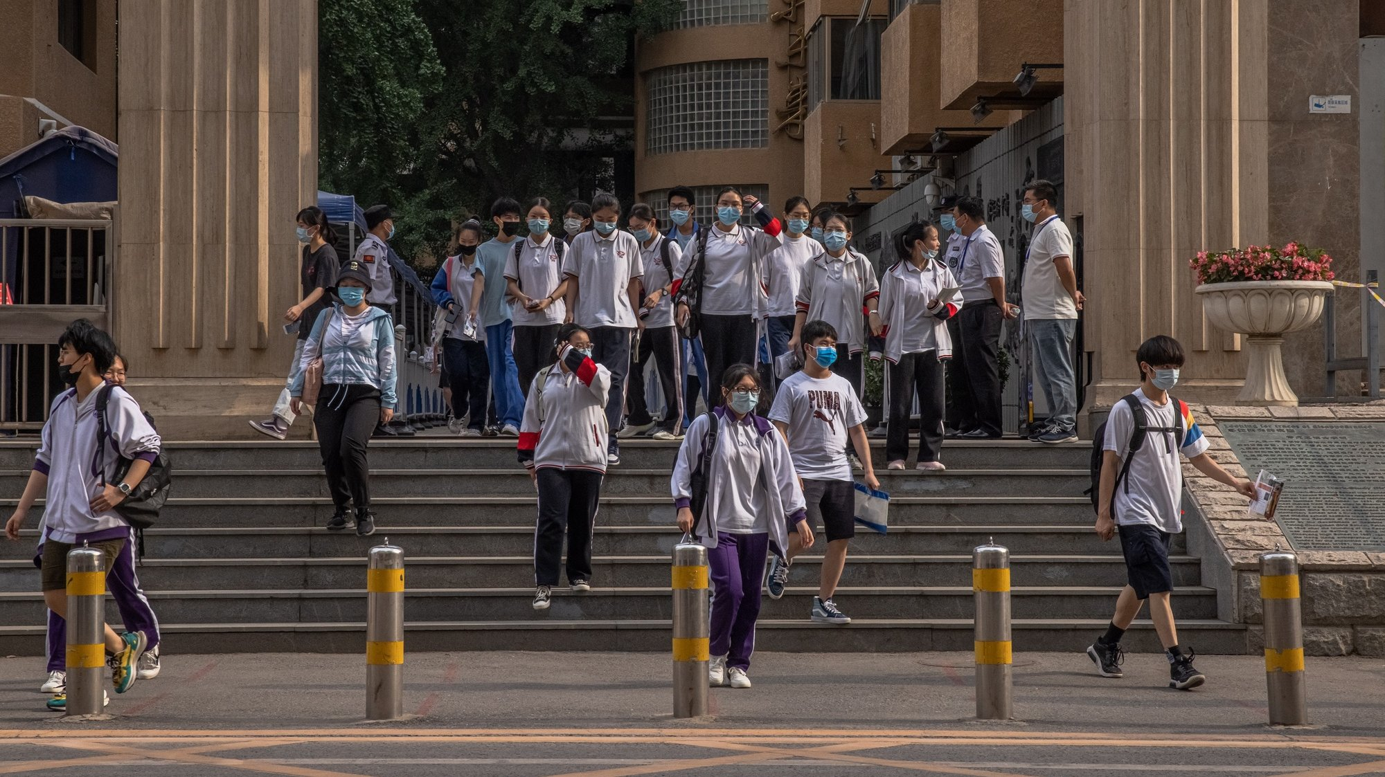 epa09254466 Students wearing protective face masks leave a school after the last exam on the final day of China's annual national college entrance examinations, in Beijing, China, 08 June 2021. China's annual national college entrance examination, commonly known as Gaokao usually takes place in June. This year examinations began 07 June and lasted for two days with around 10.8 million students across the country attending it.  EPA/ROMAN PILIPEY