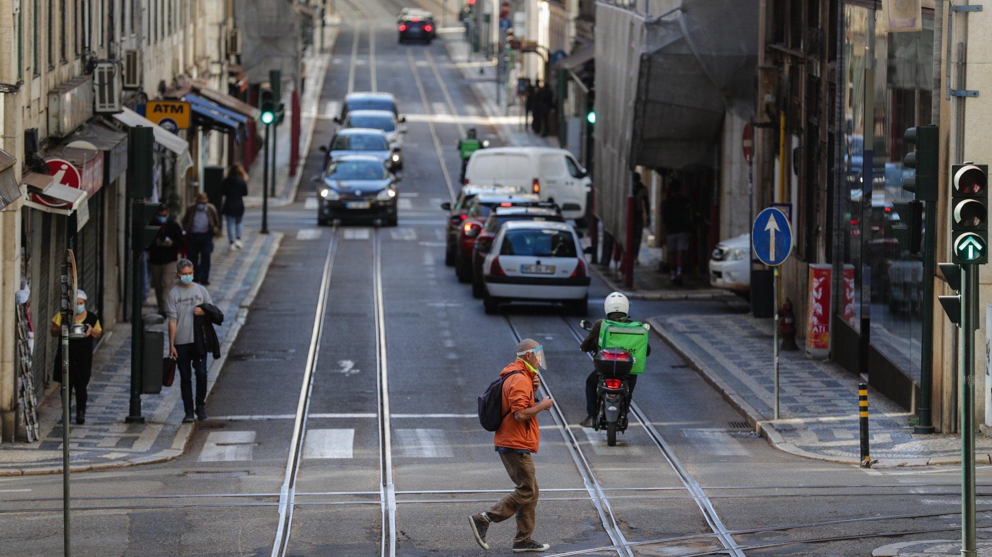 Um traseunte atravessa a rua na zona da baixa pombalina de Lisboa, 20 de novembro de 2020. A falta de turismo na cidade de Lisboa devido à pandemia de Covid 19 levou a que muitos estabelecimentos comerciais, alguns deles emblemáticos e de familias há gerações estejam em risco de fechar. (ACOMPANHA TEXTO DA LUSA DE 22 DE NOVEMBRO DE 2020) TIAGO PETINGA/LUSA