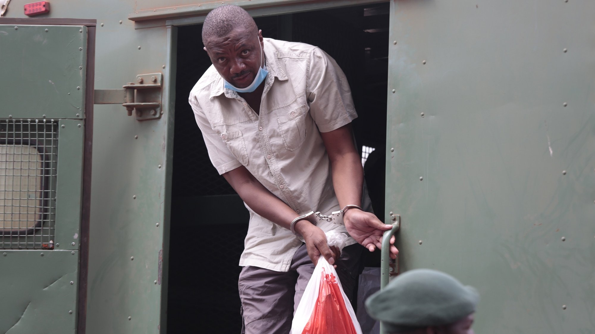 epa08802249 Freelance journalist Hopewell Chin'ono gets off a prisons truck as he arrives in handcuffs and leg irons at the Harare Magistrates Courts in Harare, Zimbabwe, 06 November 2020.  Chin'ono was arrested on 03 November 2020 over allegations of contempt of court according to the police.  EPA/AARON UFUMELI