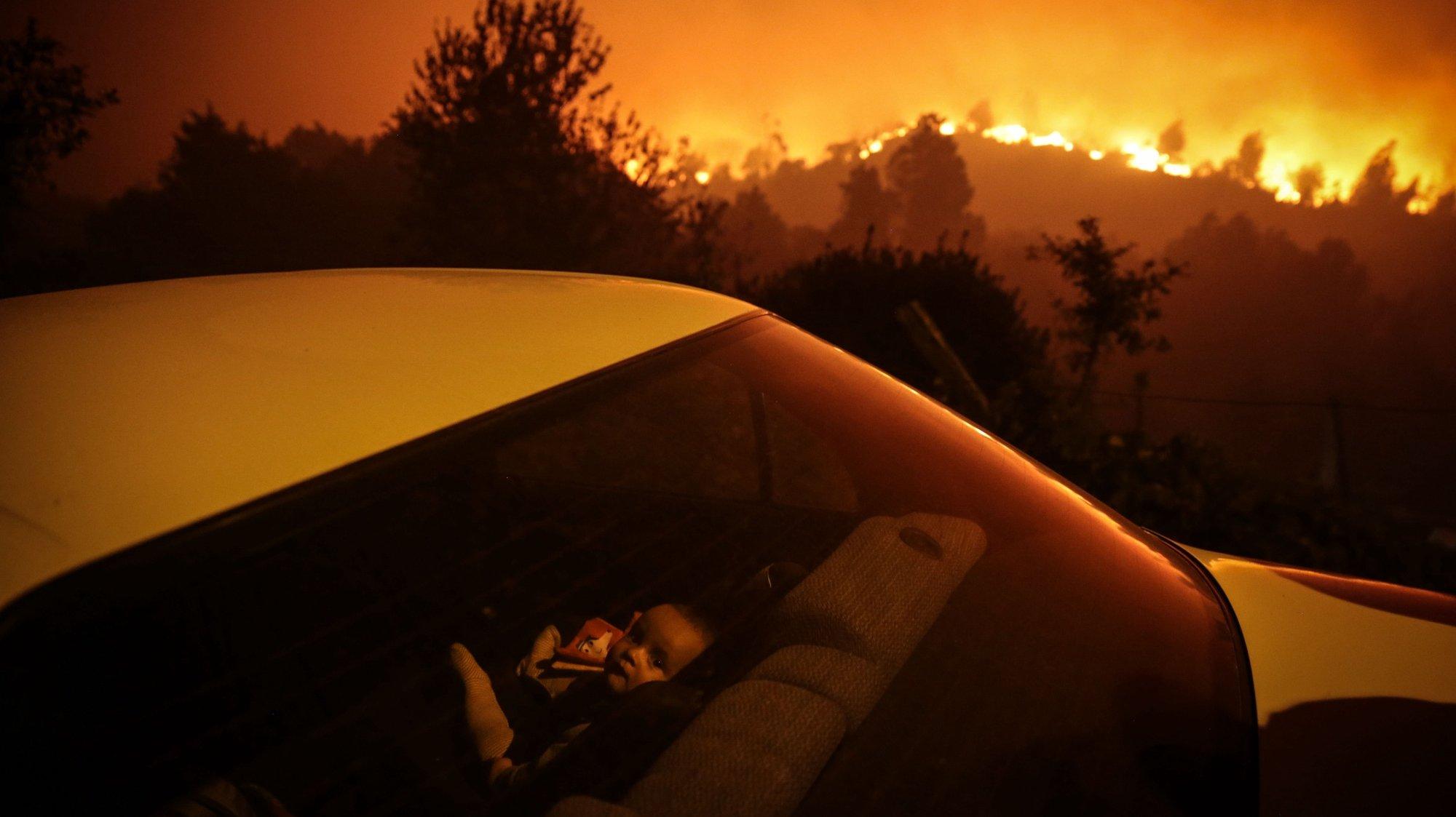 Uma criança aguarda dentro de um carro ao pé dàs chamas que consomem floresta durante um incêndio em Oliveira de Frades, 7 de setembro de 2020. Este incêndio no concelho de Oliveira de Frades, no distrito de Viseu, mobilizou 327 bombeiros, apoiados por 103 viaturas e oito meios aéreos. NUNO ANDRÉ FERREIRA/LUSA