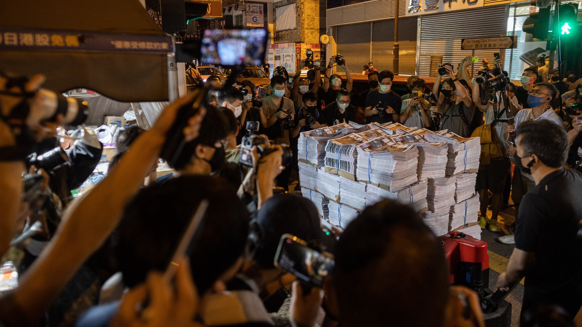 epa09296913 Supporters and members of the media surround a palette of Apple Daily's final issue being delivered to a newsstand in the early hours to buy Apple Daily's final issue in Mongkok district, Hong Kong, China, 24 June 2021. The last edition of Apple Daily rolled off the presses three days earlier than expected, after management took into consideration the safety of its staff and manpower concerns.  EPA/JEROME FAVRE