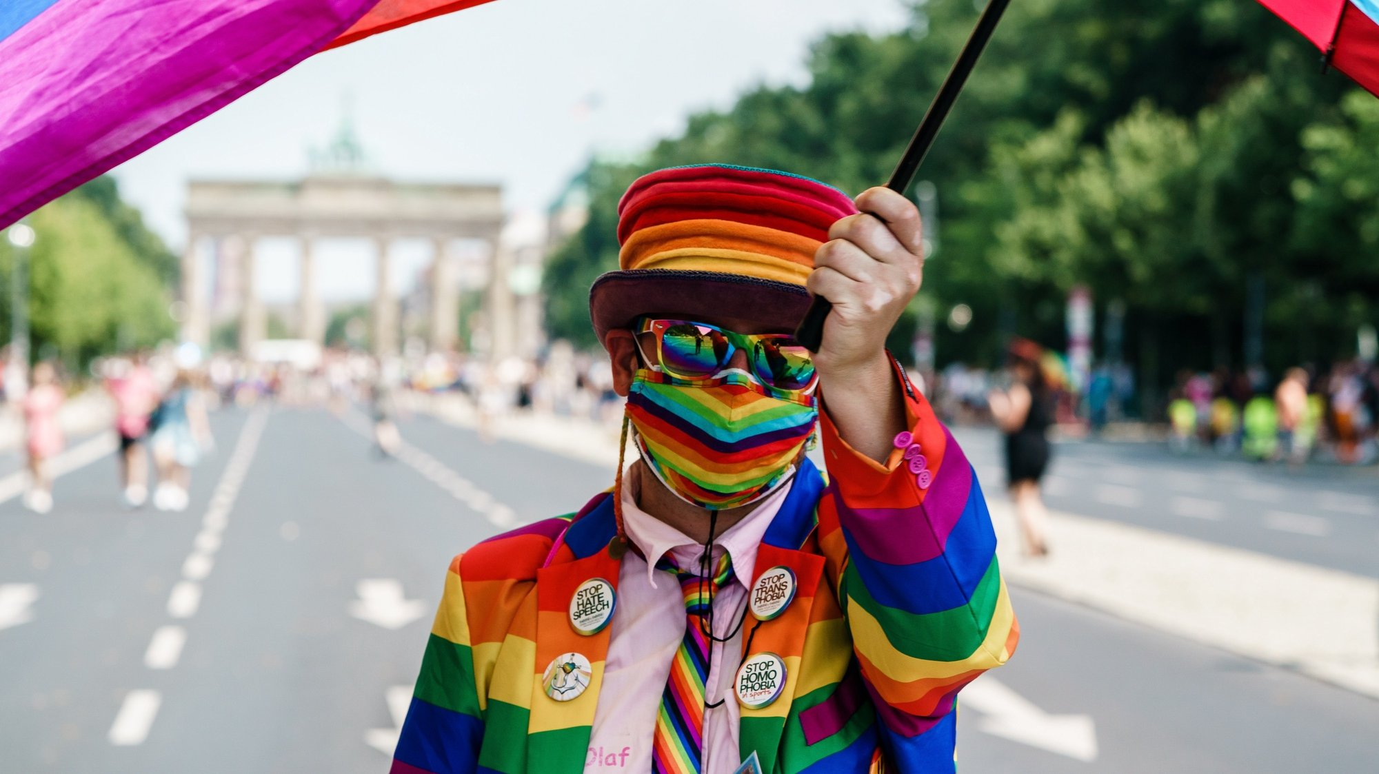 epa09362321 A participant dressed in rainbow colors waves a colorful veil attached to an umbrella in front of the Brandenburg Gate during the 'CSD Berlin 2021' Christopher Street Day parade in Berlin, Germany, 24 July 2021. Due to the Coronavirus pandemic that causes the Covid-19 disease, this year's CSD demonstration only consists of five trucks and an expected crowd of some 20,000 participants. CSD is an annual European LGBTIQA* (lesbian, gay, bisexual, transgender, intersex, queer/questioning, asexual) celebration held in various cities across Europe for the rights of LGBTIQA* people.  EPA/CLEMENS BILAN