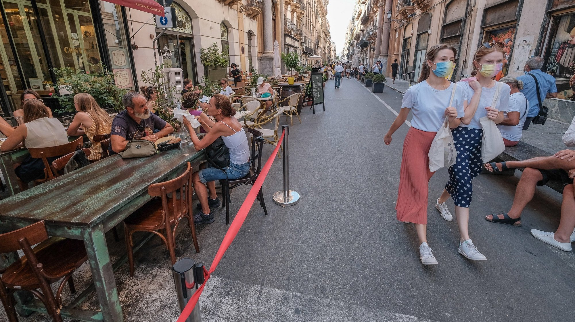 epa09437085 Tourists wear protective face masks in the centre of Palermo, Sicily island, southern Italy, 30 August 2021. Sicily from today passes from the white to the yellow zone of restrictions. Mandatory masks outdoors and a limit of four diners at the restaurant table are the most important restrictions related to the new classification.  EPA/IGOR PETYX