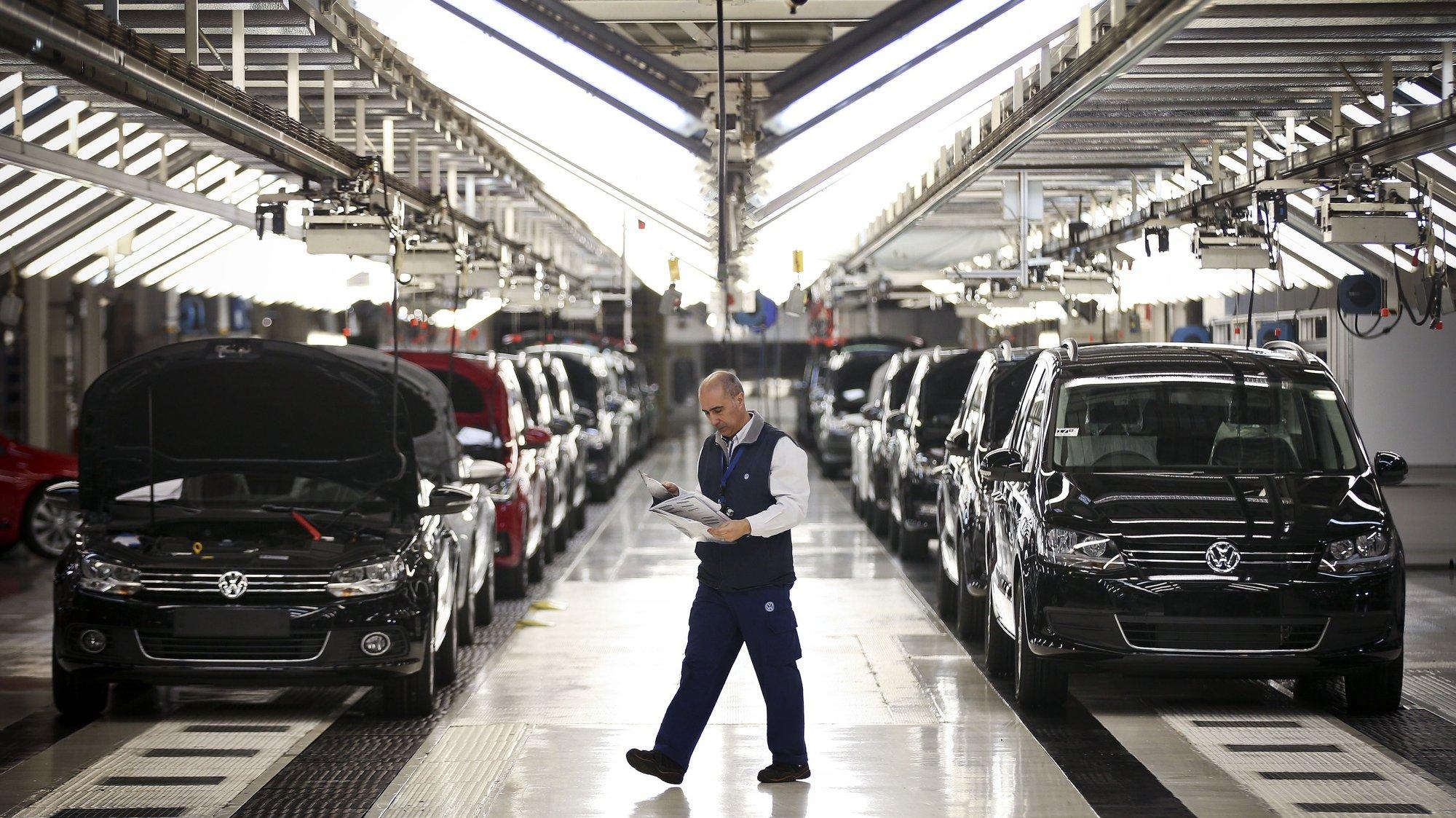 Um trabalhador da fábrica Autoeuropa do grupo alemão Volkswagen passa pela linha de sáida de veículos produzidos numa altura em que se celebram os 20 anos do início da produção da Autoeuropa em Portugal, em Palmela, concelho de Setúbal, 26 de abril de 2015. (ACOMPANHA TEXTO) MÁRIO CRUZ/LUSA