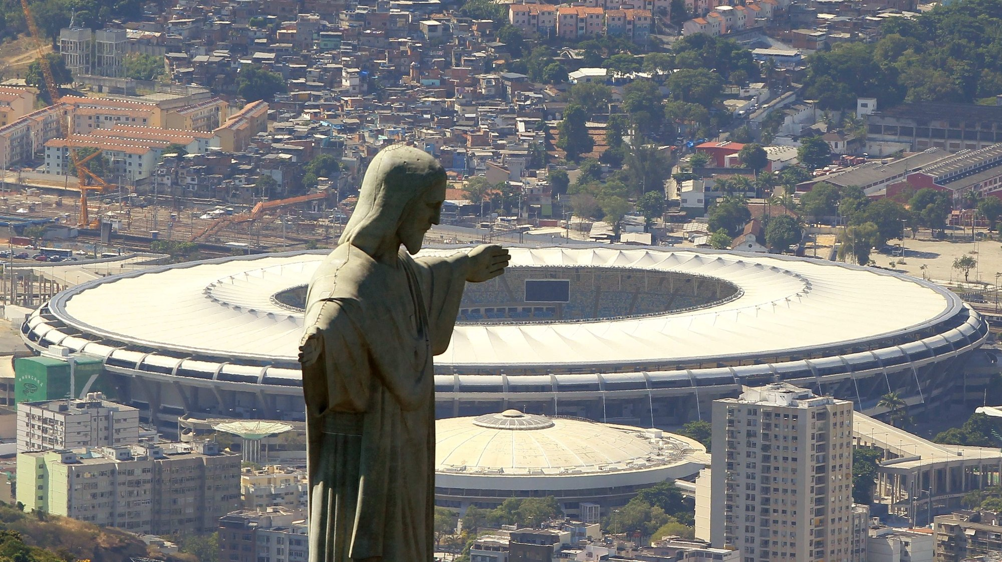 epa04141445 Picture taken on 07 February 2014 shows an aerial view of the Christ the Redeemer (Cristo Redentor) statue in front of Estadio do Maracana in Rio de Janeiro, Brazil. Once the largest stadium in the world, packing in crowds of up to 200,000, the Maracana now has an official capacity of 76,804 spectators and still remains Brazil's biggest soccer ground. Rio de Janeiro is one of the host cities of the FIFA World Cup 2014 hosting four matches in the tournament's group phase, one round of 16, one quarter final and the final match on 13 July 2014. The 20th FIFA World Cup will take place in Brazil from 12 June to 13 July 2014.  EPA/MARCELO SAYAO *** Local Caption *** 50624017