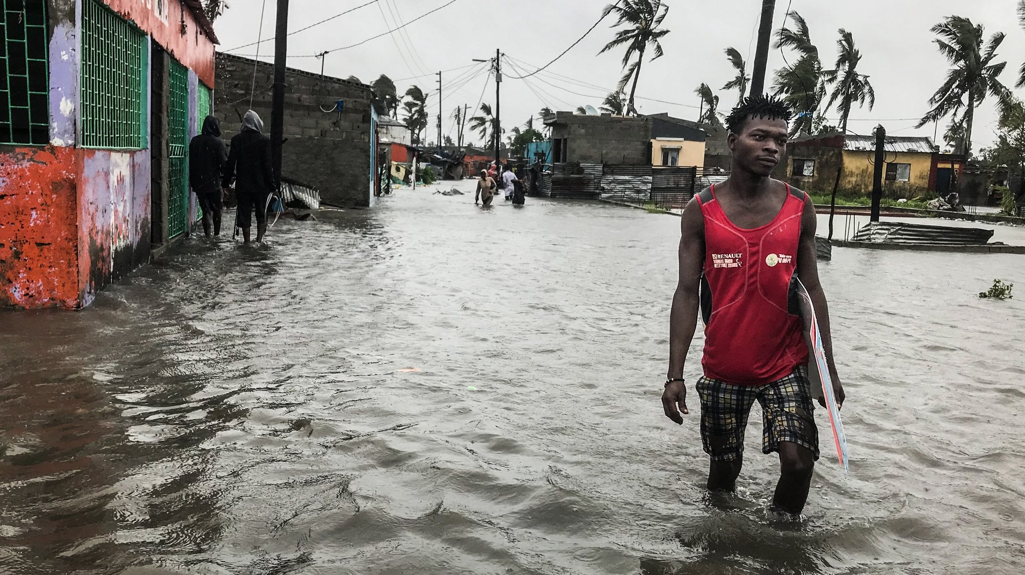 epaselect epa08959345 A man wades through flood water in the city of Beira, Mozambique, 23 January 2021, after the passage of Tropical Cyclone Eloise. The city of Beira presented signs of destruction in all streets on the day, with several flooded neighborhoods with residents circulating with the water around the waist at some points following the passage of Tropical Cyclone Eloise.  EPA/JOSE JECO