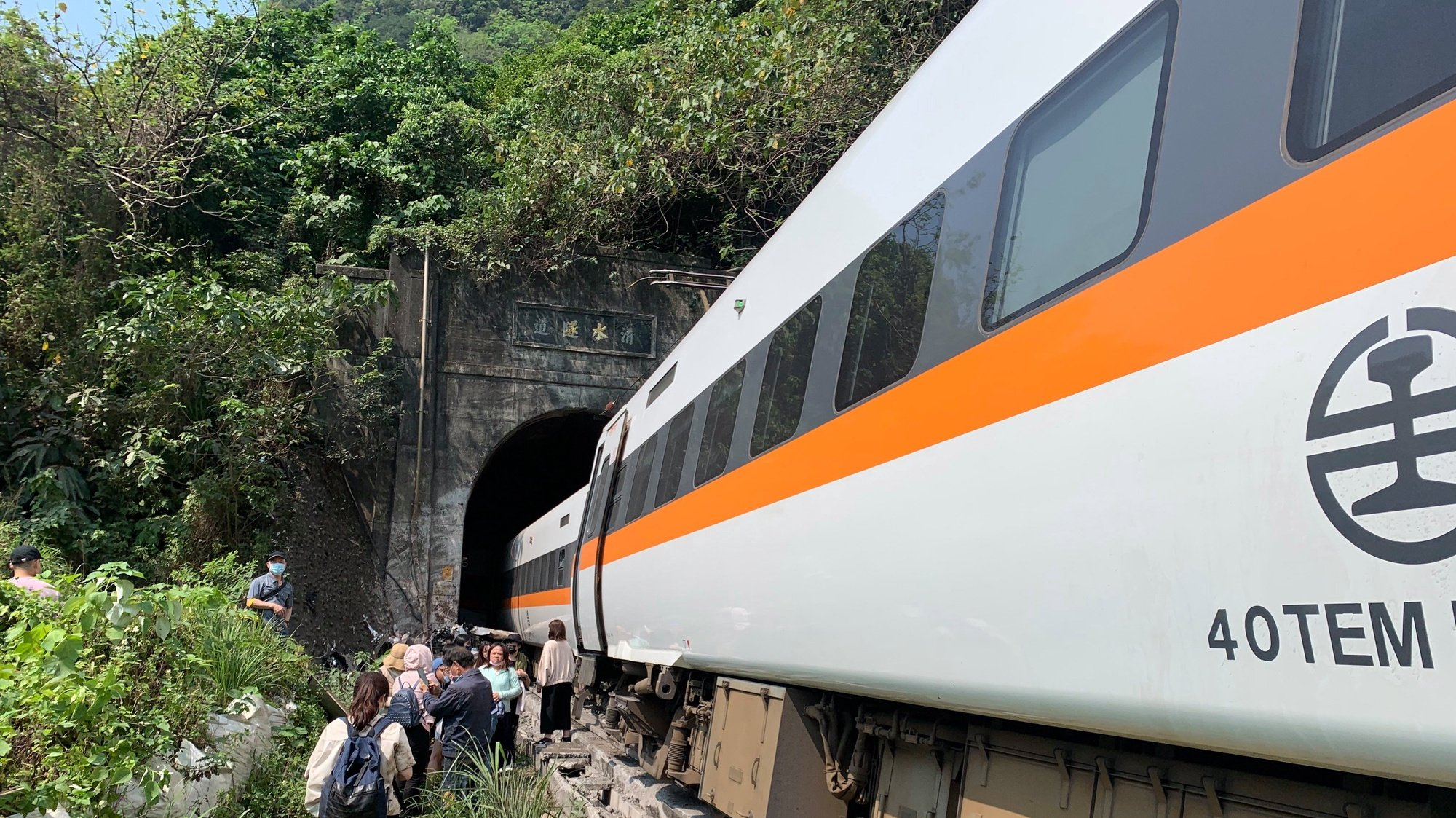 epa09111574 A handout photo made available by Taiwan's National Fire Agency shows people walking beside a train which derailed in a tunnel north of Hualien County, eastern Taiwan, 02 April 2021. At least 36 people died and many others were injured when a train carrying 350 people derailed in a tunnel north of Hualien in eastern Taiwan on 02 April.  EPA/Taiwan National Fire Agency HANDOUT  HANDOUT EDITORIAL USE ONLY/NO SALES