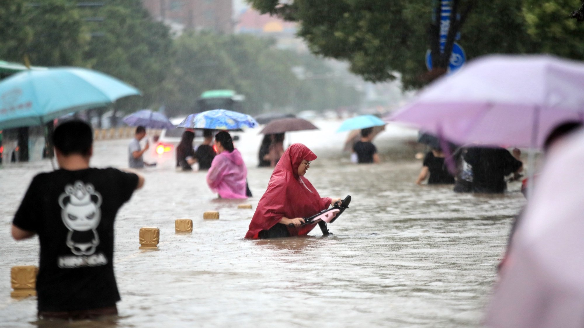 epa09356174 People walk in the flooded road after record downpours in Zhengzhou city in central China's Henan province Tuesday, July 20, 2021 (issued 21 July 2021). Heavy floods in Central China killed 12 in Zhengzhou city due to the rainfall yesterday, 20 July 2021, according to official Chinese media. Over 144,660 people have been affected by heavy rains in Henan Province since July 16, and over 10,000 had to be relocated, the provincial flood control and drought relief headquarters said Tuesday.  EPA/FEATURECHINA CHINA OUT