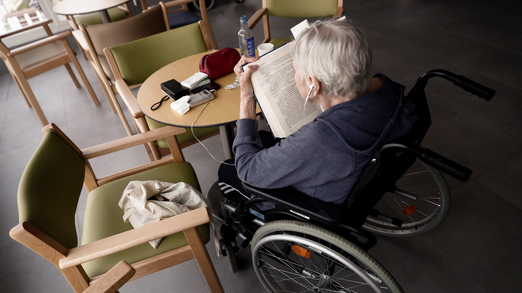 epaselect epa08356843 A resident sits in a wheelchair while reading a Spanish translation of the popular book 'The Adventures of Sherlock Holmes' by Sir Arthur Conan Doyle in a common area of the Casablanca retirement home in the working-class district of Villaverde, Madrid, Spain, 11 April 2020. Despite almost all countries adopting specific measures to protect nursing homes from the ongoing pandemic of the COVID-19 disease caused by the SARS-CoV-2 coronavirus, they have become one of the main foci of infection, with their elderly residents constituting the main at-risk group that is especially vulnerable to the virus' devastating spread. Retirement homes across Spain are recording some of the highest figures when it comes to COVID-19 infections and mortality rates.  EPA/MARISCAL