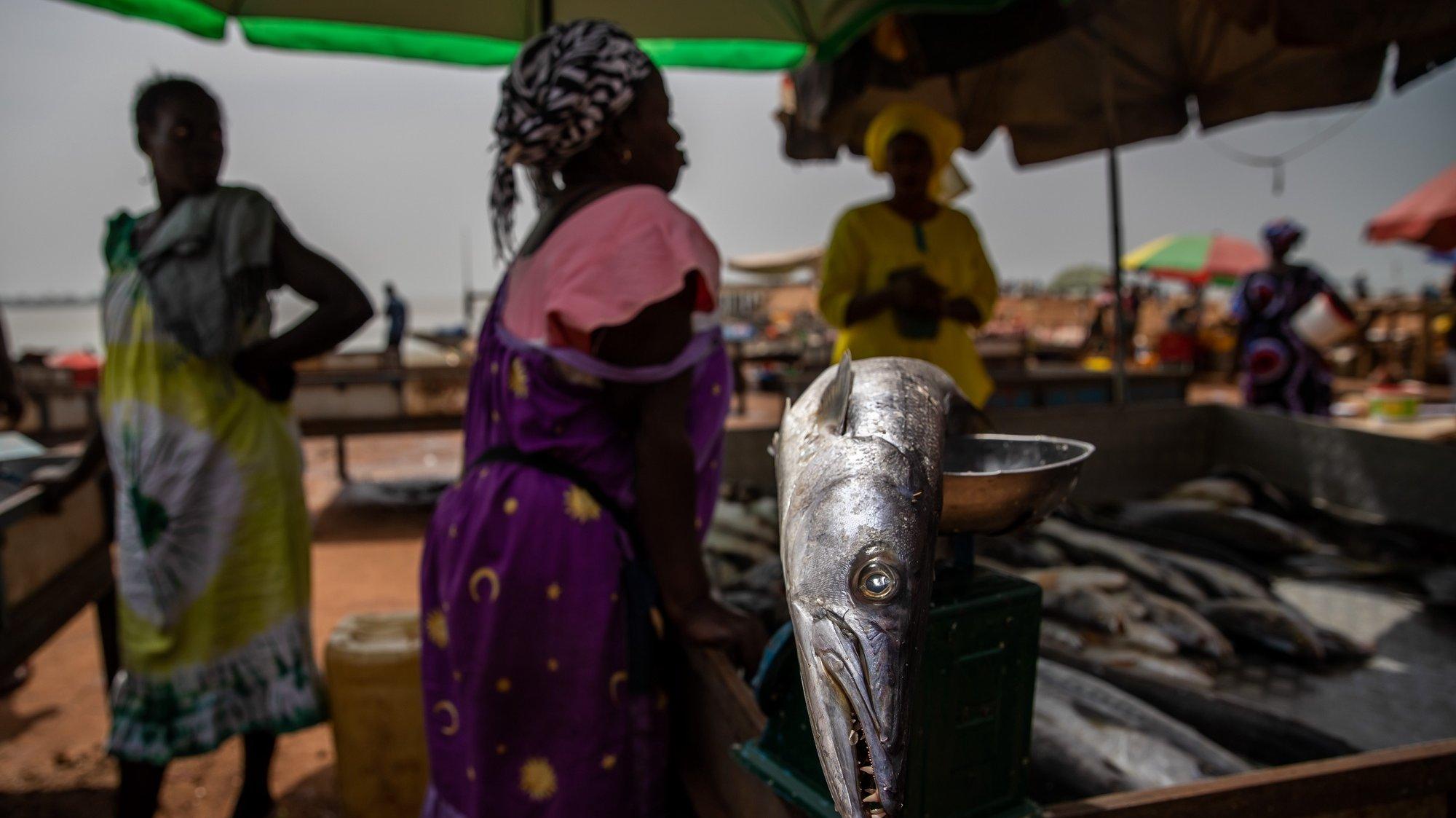 Comerciantes e populares negoceiam no mercado de peixe no Porto de Bissau, na Guiné-Bissau, 17 de maio de 2021. JOSÉ SENA GOULÃO/LUSA