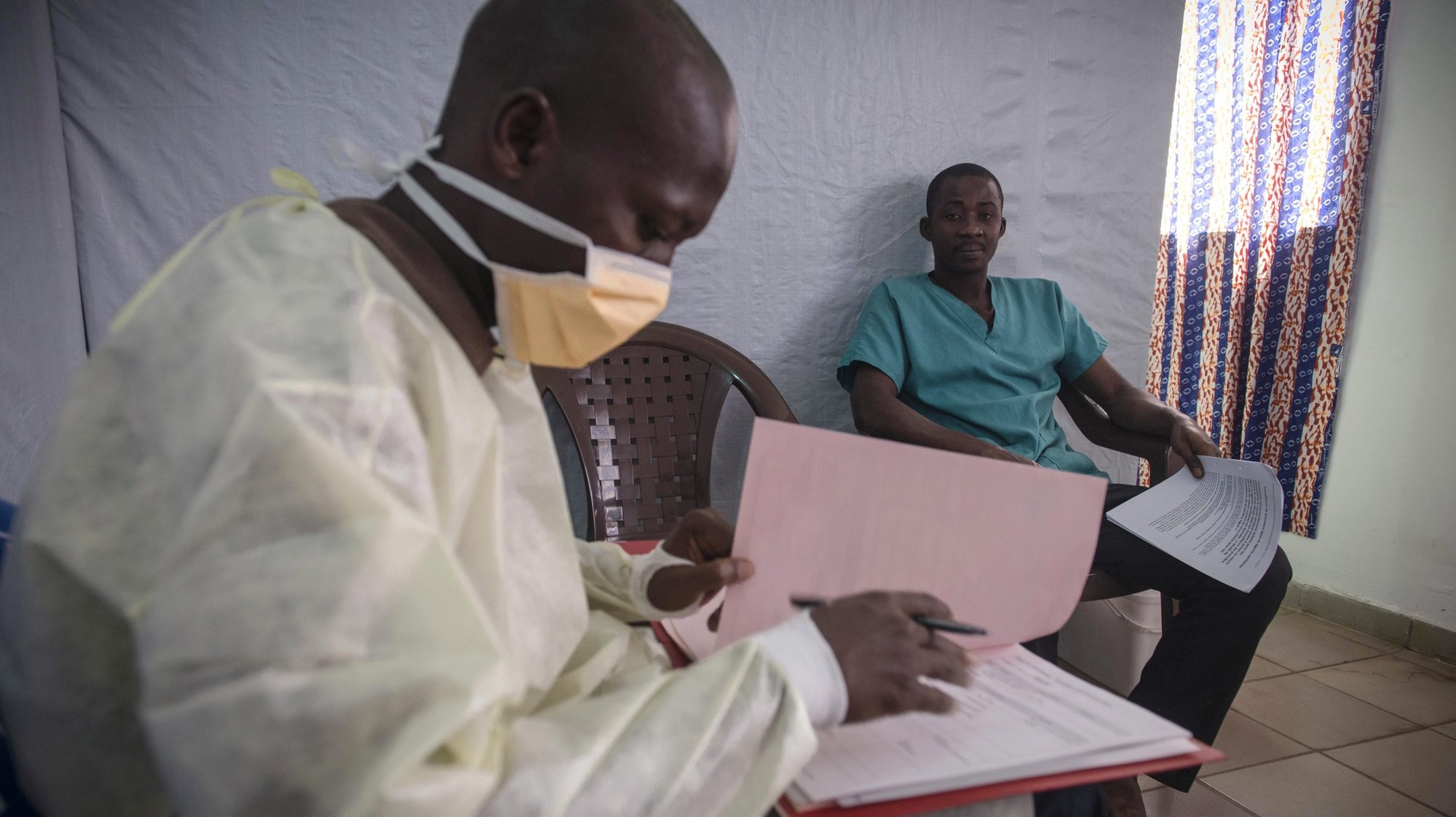 epa04868020 A handout image released by Medecins Sans Frontiers (MSF) showing a volunteer Ebola frontline worker answering a questionnaire before receiving the rVSV-EBOV experimental vaccine against Ebola at the vaccination clinic, inside Donka Hospital compound, Conakry, Guinea, 31 July 2015. A medical journal report indicates the initial trial showed success against contraction of the virus in test group who had confirmed exposure to infected persons and were given the vaccine immediately while amongst another group given the vaccine after a 10-day delay showed more than a dozen cases.  EPA/YANN LIBESSART / MSF / HANDOUT  HANDOUT EDITORIAL USE ONLY/NO SALES