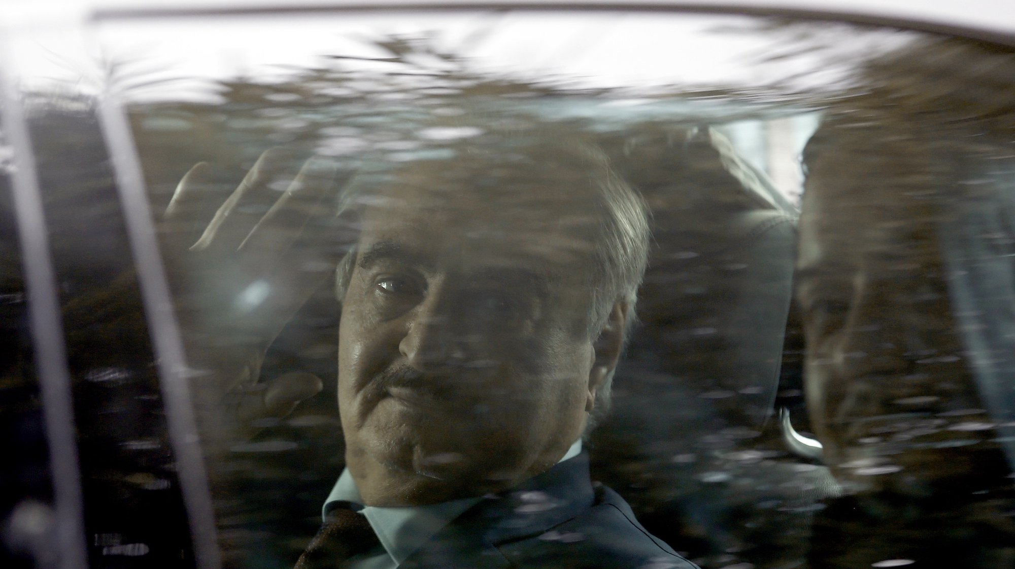 epa08135423 A security guard is seen reflected on a window's car as Commander of the Libyan National Army (LNA) Khalifa Haftar waves to phojournalists from inside a car as he leaves after his meeting with Greek Foreign Ministrer Dendias in Athens, Greece, 17 January 2020. Gen. Haftar is visiting Athens where he is expected to meet with Greek Prime Minister Mitsotakis.  EPA/YANNIS KOLESIDIS