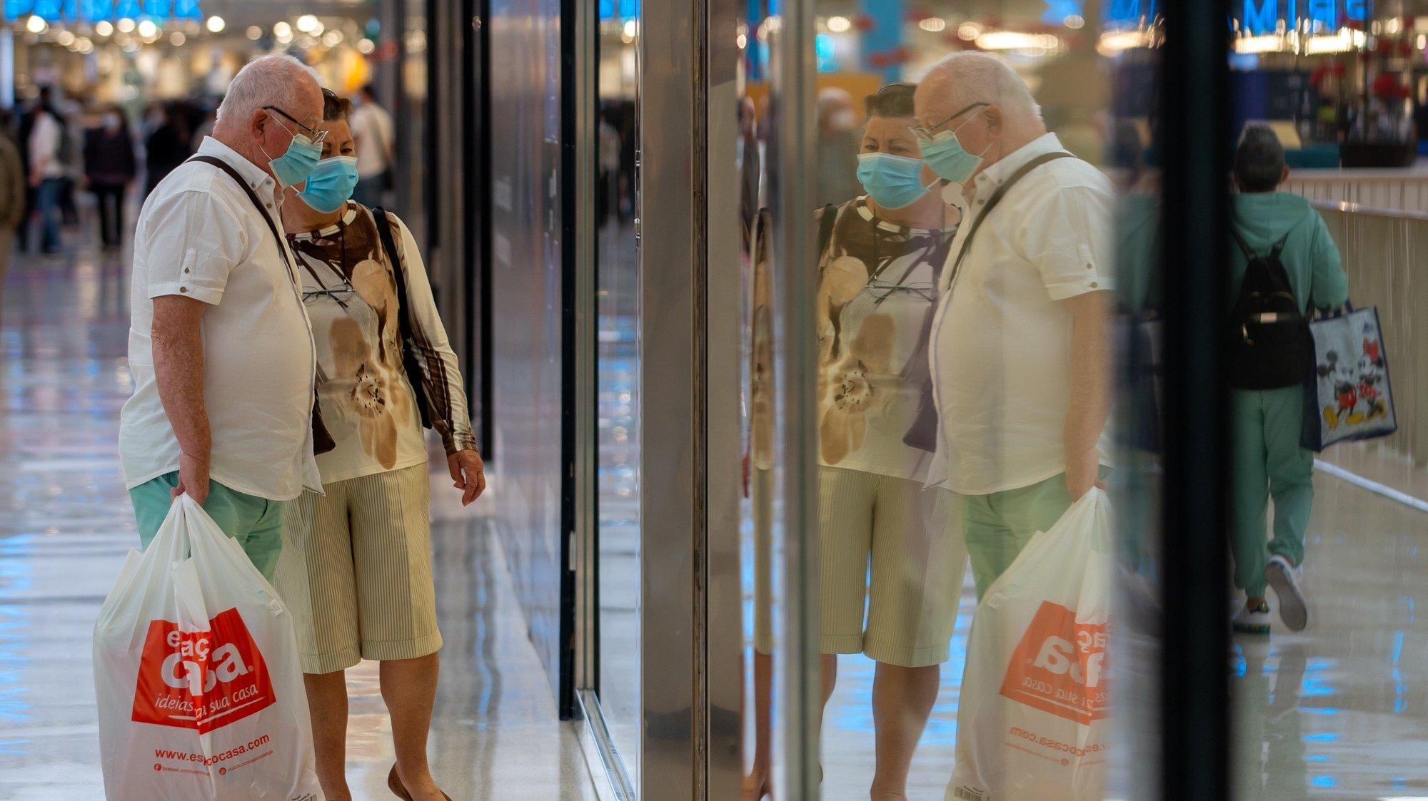 Pessoas observam as montras das lojas do Centro Comercial UBBO, no dia que marca o início da terceira fase de desconfinamento em Portugal, na Amadora, 19 de abril de 2021. Portugal inicia hoje a terceira fase do desconfinamento com a reabertura de mais escolas, lojas, restaurantes e cafés, um levantamento de restrições que não é acompanhado nos 10 concelhos onde a incidência da covid-19 é maior. JOSÉ SENA GOULÃO/LUSA