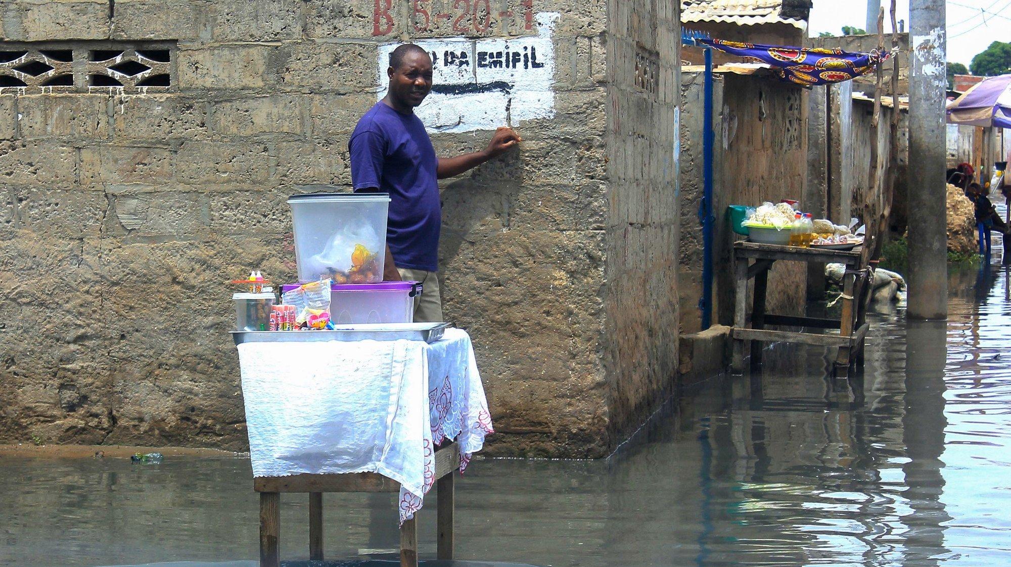Um vendedor ambulante vende os seus produtos numa rua alagada do Bairro da Boa Esperança após a queda de chuvas fortes na capital angolana, Luanda, Angola, 9 de abril de 2019.  AMPE ROGÉRIO/LUSA
