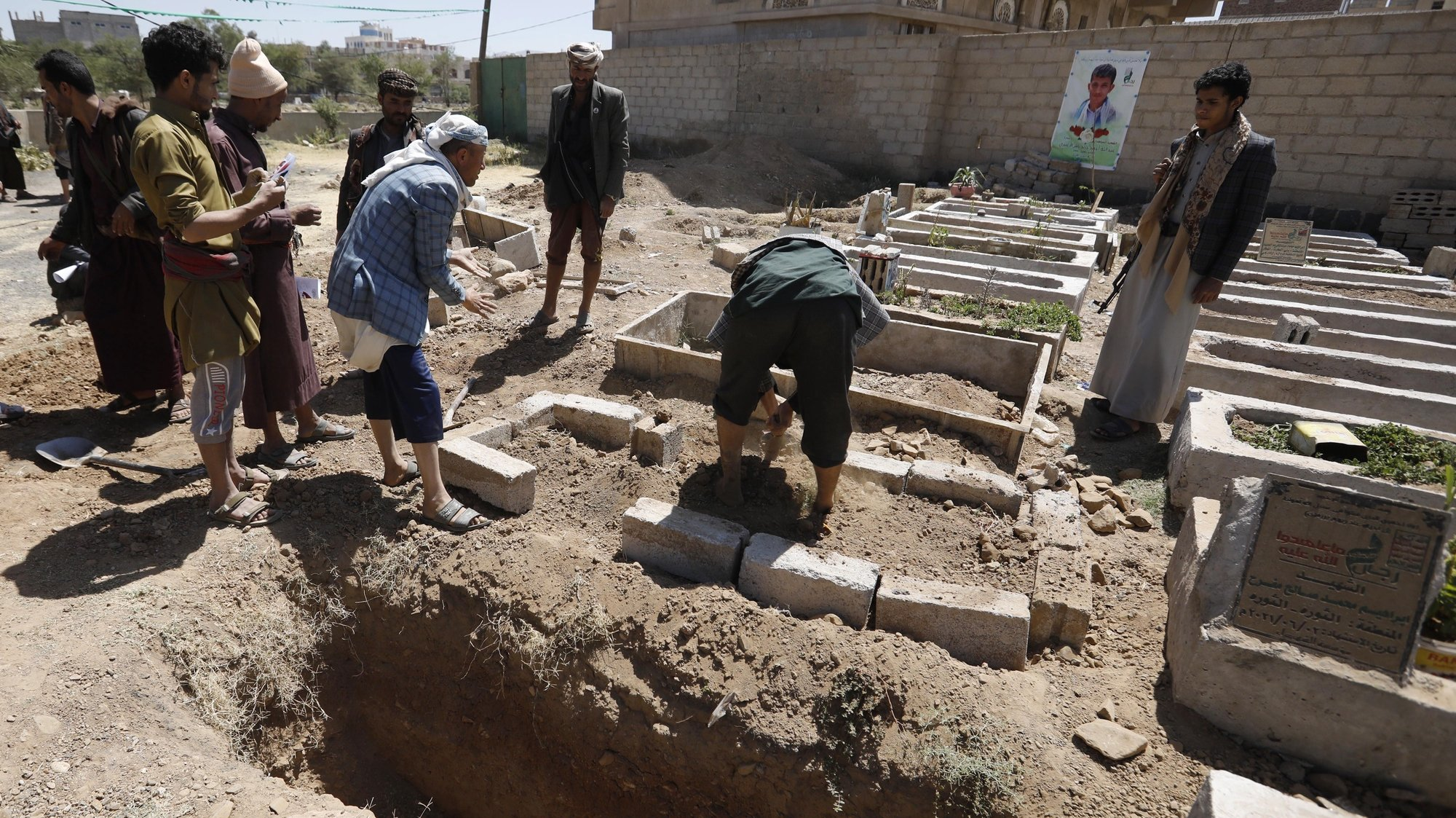 epa09527254 Yemenis bury the body of a slain Houthi fighter near a freshly dug grave during a funeral at a cemetery dedicated to slain Houthi fighters, in Sana'a, Yemen, 16 October 2021. Saudi-led coalition's airstrikes have allegedly targeted Houthi reinforcements heading to the front lines in the Yemeni province of Marib, killing more than 180 Houthi fighters in the past two days as the Houthis intensify their offensive in quest for control of the oil-rich province, the Yemeni government's last northern stronghold. The UN has estimated that at least 235 civilians were killed or injured during hostilities in Yemen in September 2021, the second highest monthly death toll in two years of ongoing conflict and the Saudi-led bombing campaign.  EPA/YAHYA ARHAB
