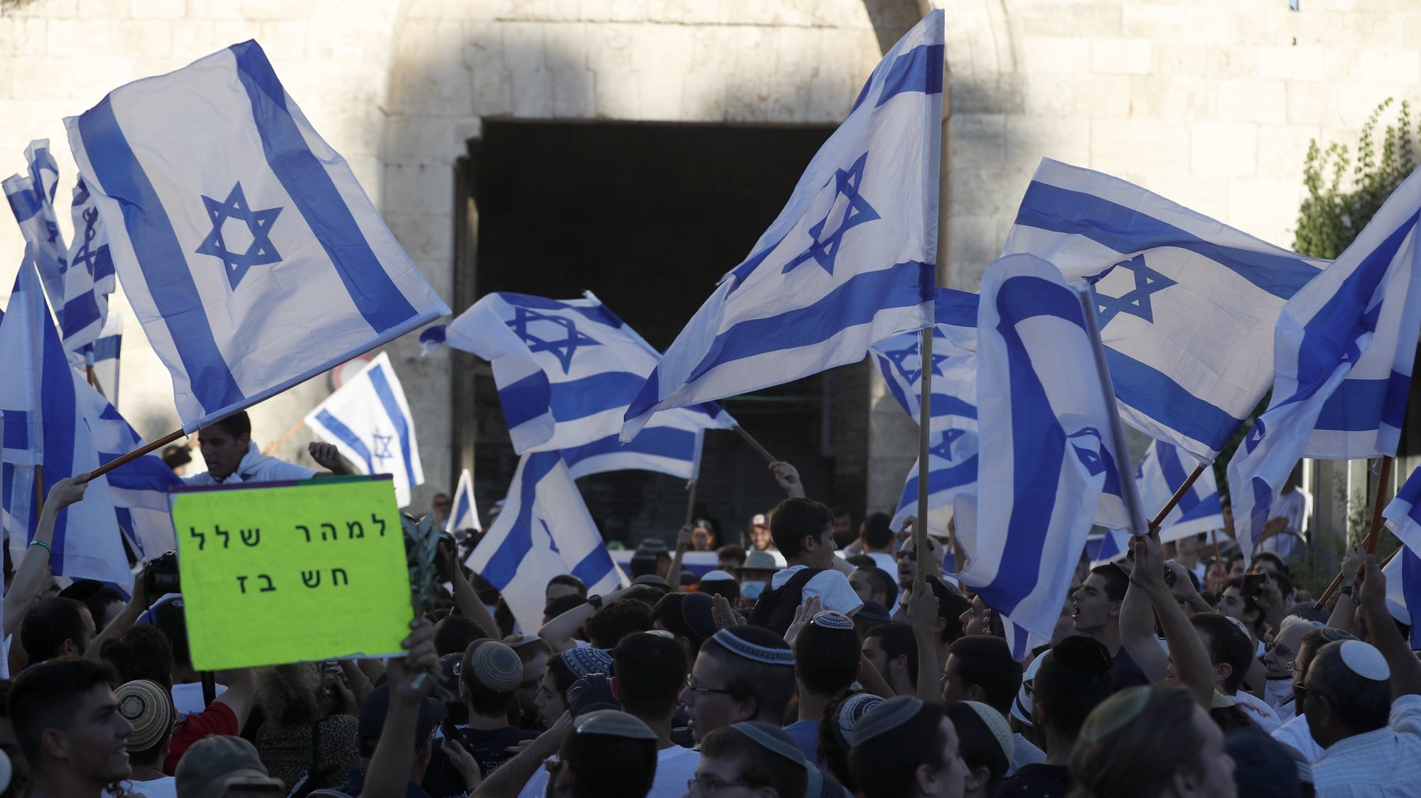 epa09274157 Members of Israeli right-wing groups taking part in the 'Flag March' wave Israeli flags next to Damascus gate of Jerusalem's Old City, 15 June 2021. Media reports state that more than 2,500 Israeli police were deployed to secure the march and the Israeli army is preparing for the possibility of another escalation with Gaza.  EPA/ATEF SAFADI