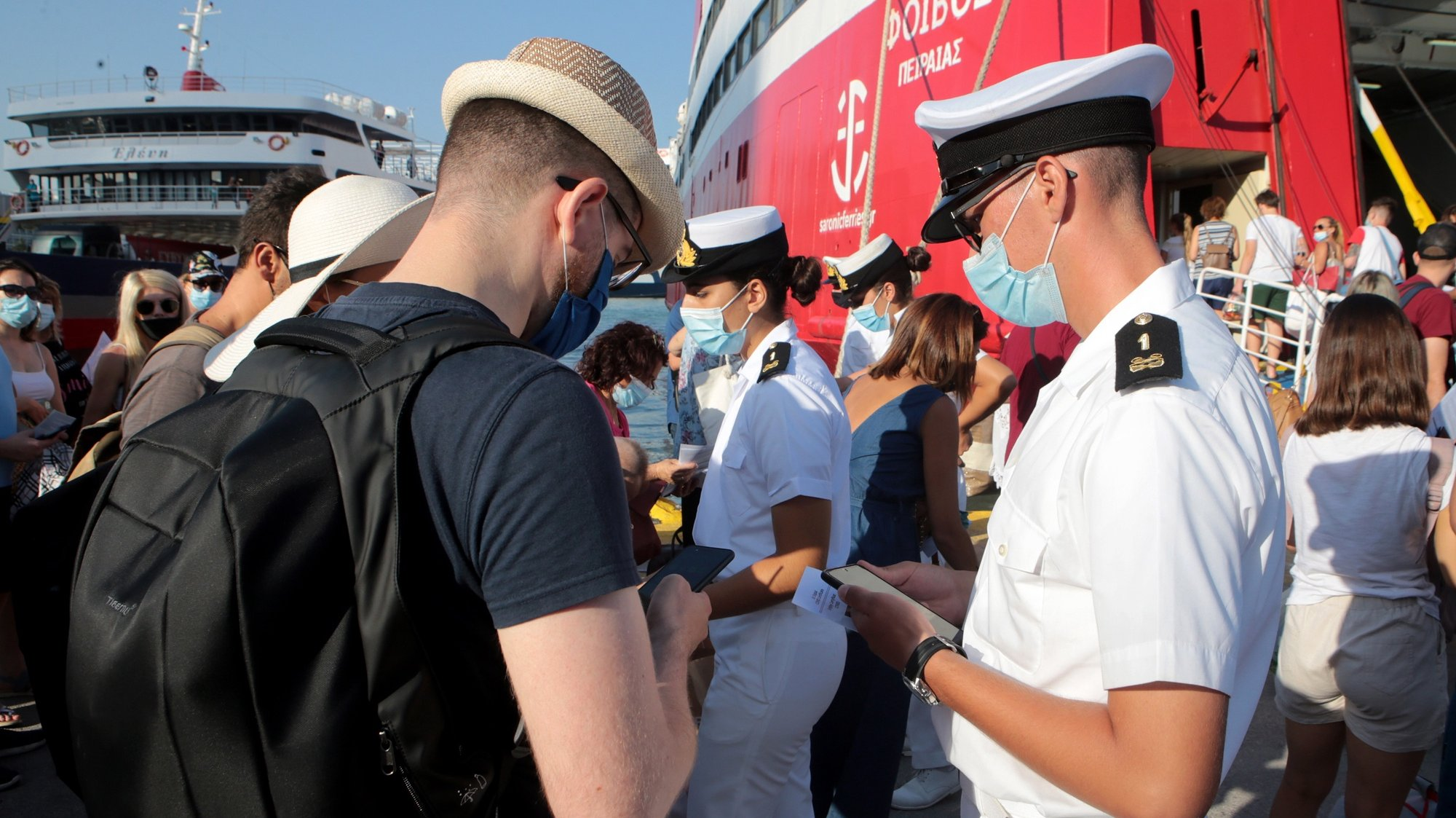 epa09348069 Officers of the Hellenic Coast Guard check passengers documents at the port of Piraeus, near Athens, Greece, 16 July 2021. The Hellenic Coast Guard take over the checks that passengers boarding ships comply with Covid rules as of July 16th, according to a decision made by Greek Shipping and Island Policy Minister Yiannis Plakiotakis with the coast guard leadership. Minister said this will ensure that checks are thorough and vouchsafe the maximum possible protection of the passengers' health.  EPA/PANTELIS SAITAS