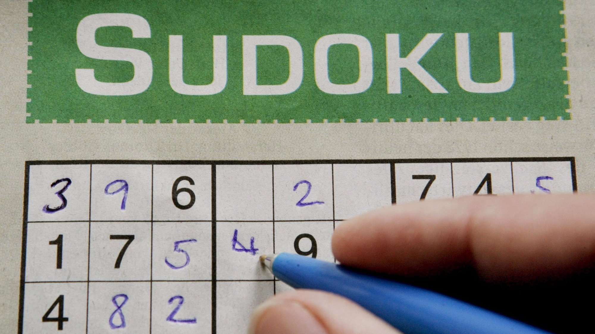 epa000509159 A woman fills in the grid of a Sudoku puzzle in a newspaper, Frankfurt, Germany, Monday 22 August 2005. In the game, which has been becoming more and more popular in Germany as well as around the world, there is no math involved. The puzzle is solved with reasoning and logic only.  EPA/FRANK MAY