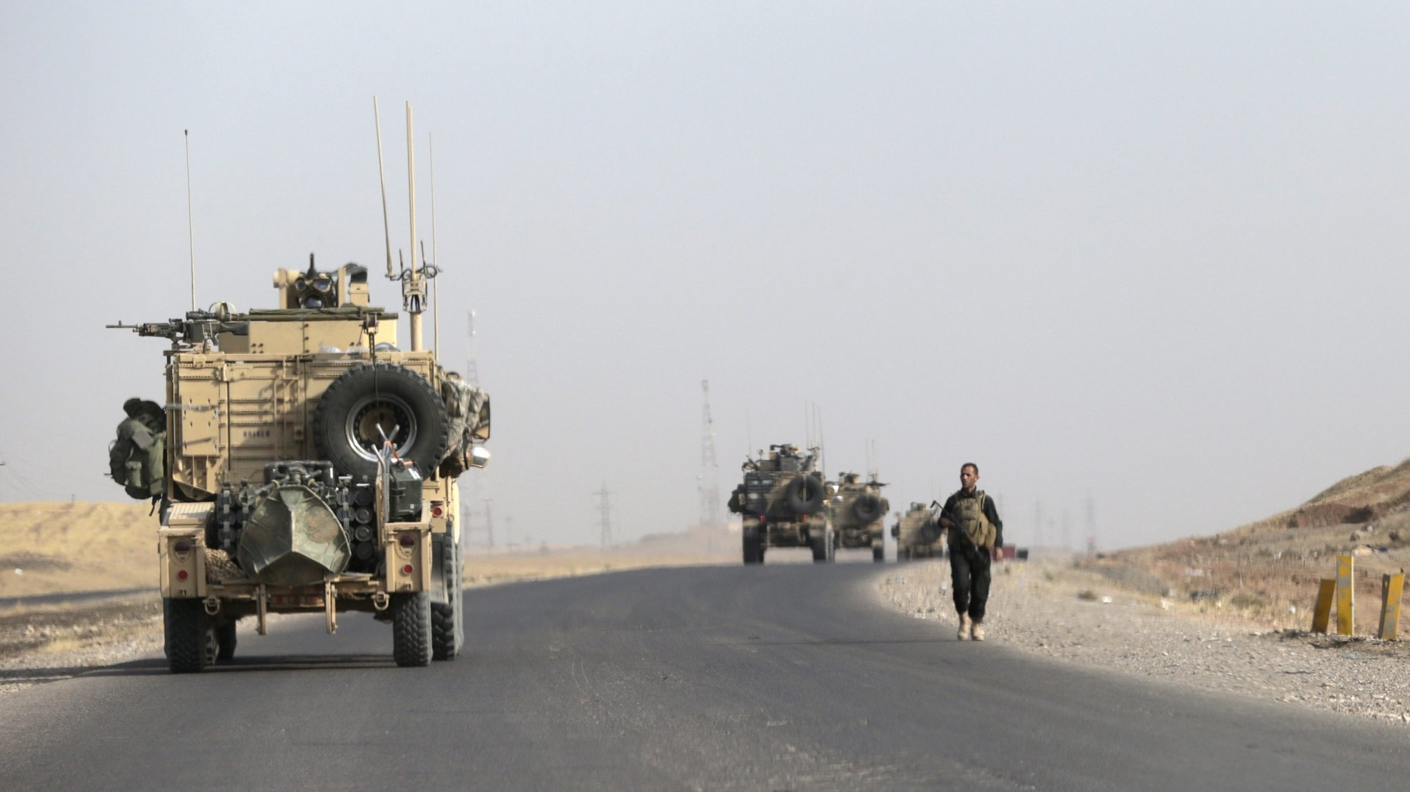 epa05596176 US Army vehicles drive past an Iraqi soldiers  near Khazir some 40km of Erbil, the capital of the region of Kurdistan, Iraq, 21 October 2016. Iraqi army forces announced on 21 October morning that they have taken full control of Bartila, and in an interview with epa, Major General Maan al-Saadi, the Commander of Partial Operation in Bartila said that there were some 100 IS fighters inside the town, 80 of them were killed. Those left have retreated to a village adjacent to Bartila on the way to Mosul and that the Special Forces were now clearing the place of the explosive devices planted by IS.  EPA/AMEL PAIN