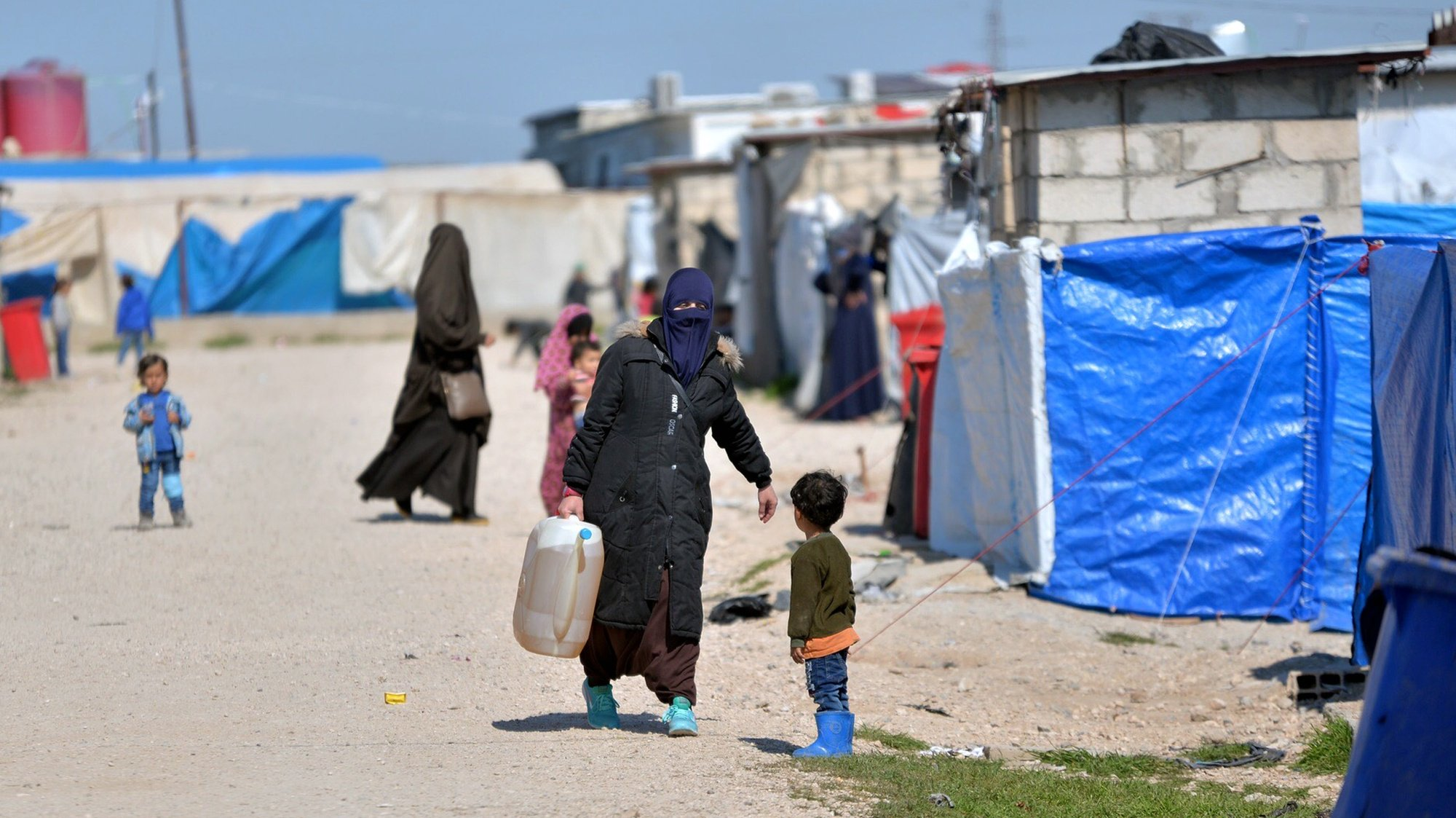 epa07393580 Displaced women walk at Roj refugees camp in Hasakah, northeast of Syria, 24 February 2019. The camp which is controlled by the US-backed Syrian Democratic Forces (SDF) houses over 300 families, most of them are wives and children of Islamic state (IS) fighters among them foreigners who arrived in the camp following the defeat of Islamic State group in its last strongholds in eastern Syria.  EPA/MURTAJA LATEEF