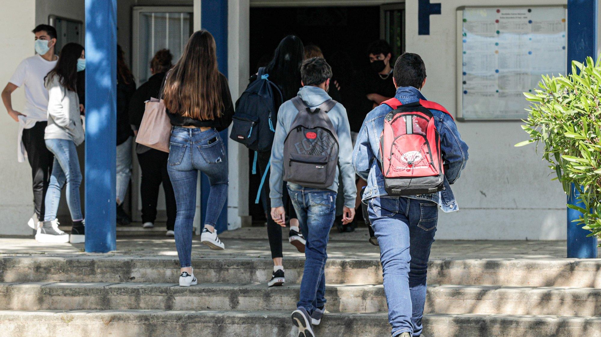 Alunos à entrada da Escola Secundária de Albufeira, no dia do regresso às aulas do ensino secundário, no âmbito das novas medidas de desconfinamento relacionadas com a pandemia da covid-19, em Albufeira, 19 de abril de 2021. Portugal inicia hoje a terceira fase do desconfinamento com a reabertura de mais escolas, lojas, restaurantes e cafés, um levantamento de restrições que não é acompanhado nos 10 concelhos onde a incidência da covid-19 é maior. LUÍS FORRA/LUSA