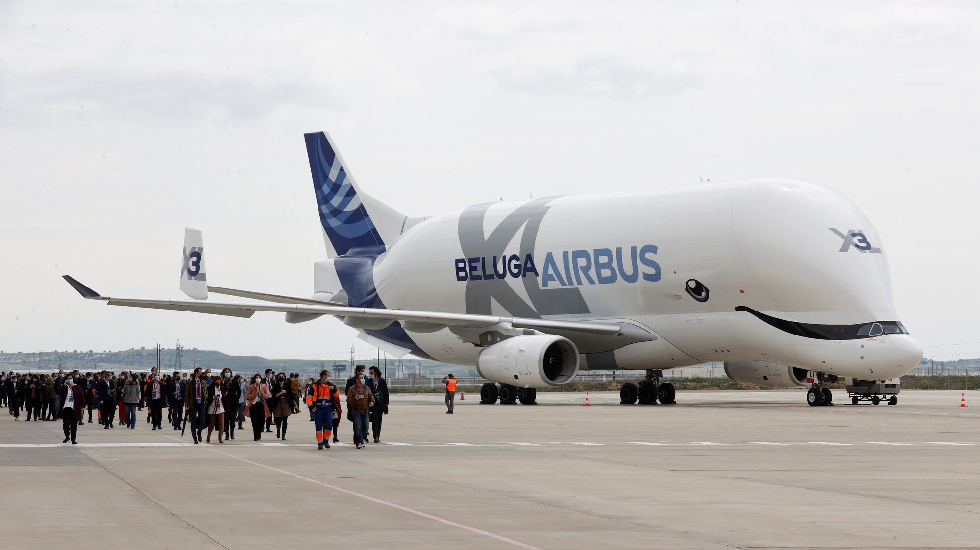 epa09136831 Several guests walk past an Airbus Beluga XL (Airbus A330-700L) aircraft during the opening of Airbus Defense and Space Campus, in the town of Getafe, outside Madrid, Spain, 15 April 2021.  EPA/Chema Moya