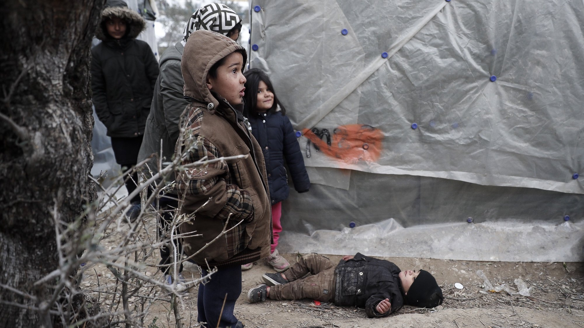 epa08767212 YEARENDER 2020 POLITICS  Refugee children outside their tent in an olive yard next to the refugee camp of Moria, on Lesvos island, Greece, 21 January 2020 (issued 22 January 2020). The entire island of Lesvos among with Chios and Samos are holding a 24-hour strike on 22 January to protest the migration situation as thousands of asylum seekers are stranded there in unbearable situation and low temperatures.  EPA/DIMITRIS TOSIDIS *** Local Caption *** 55790483