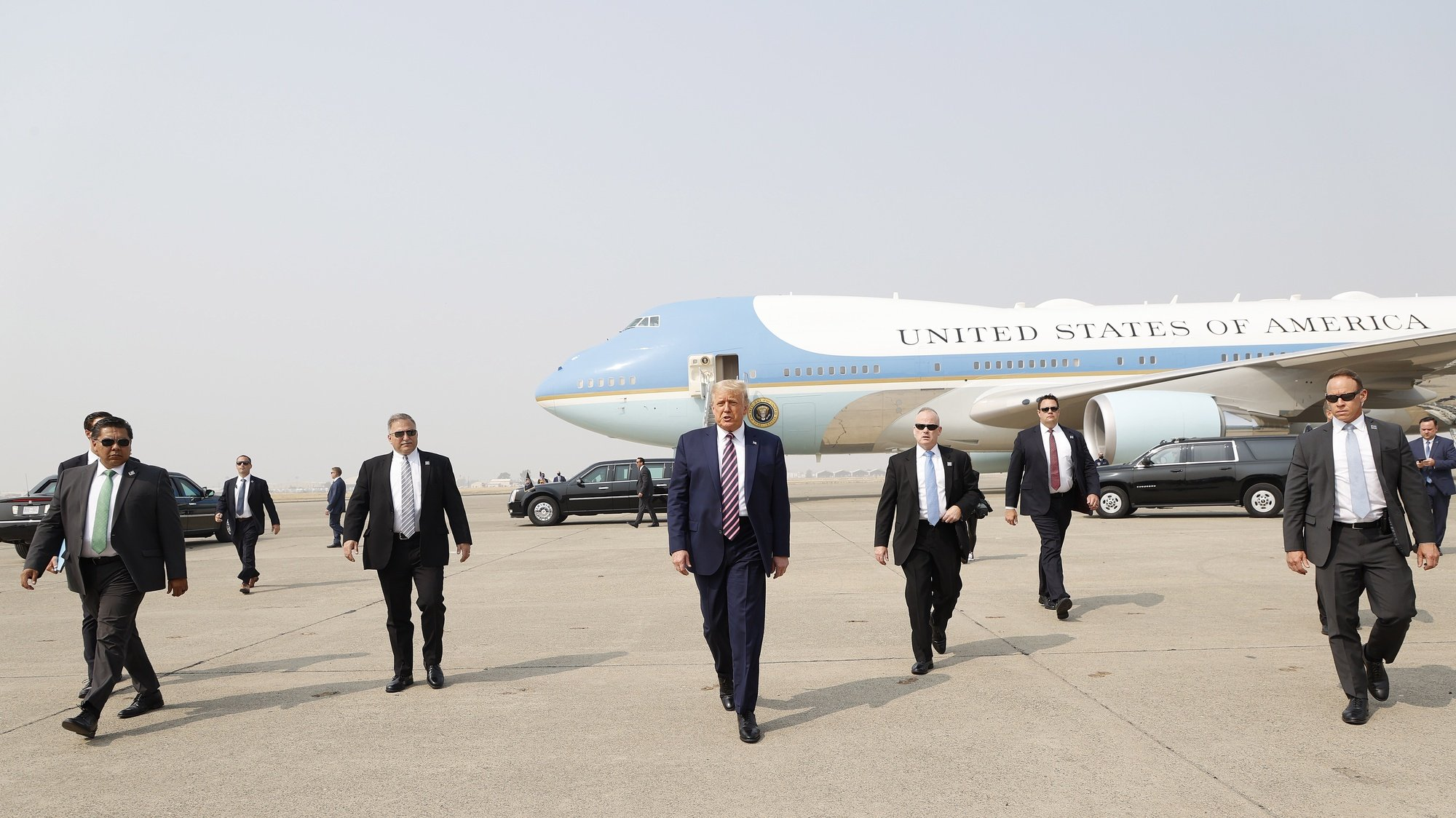 epa08939649 (FILE) US President Donald J. Trump (C) walks towards the media platform surrounded by his secret service detail after arriving on Air Force One at Sacramento McClellan Airport in McClelland Park, California, USA, 14 September 2020. The President visited Sacramento County to be briefed on the deadly wildfires that have burned more than three million acres across California. The presidency of Donald Trump, which records two presidential impeachments, will end at noon on 20 January 2021.  EPA/JOHN G. MABANGLO *** Local Caption *** 56342653
