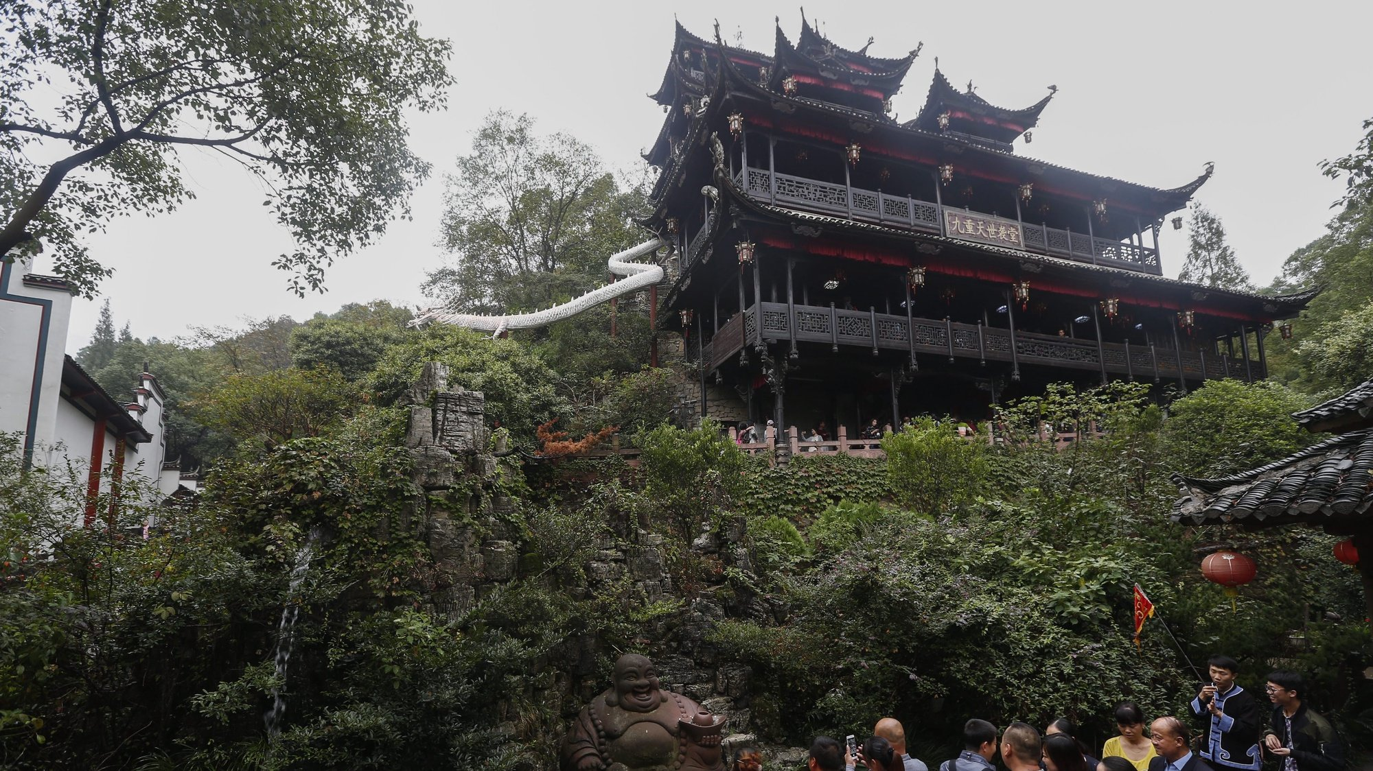 epa05595994 A wooden house designed according to the culture of the Tujia ethnic minority group stands above tourists at the Tujia Minority Castle tourist compound in Zhangjiajie City, Hunan Province, China, 21 October 2016. The Tujia are one of 33 ethnic minority groups in Zhangjiajie, a popular tourism city with a population of 1.7 million.  EPA/ROLEX DELA PENA
