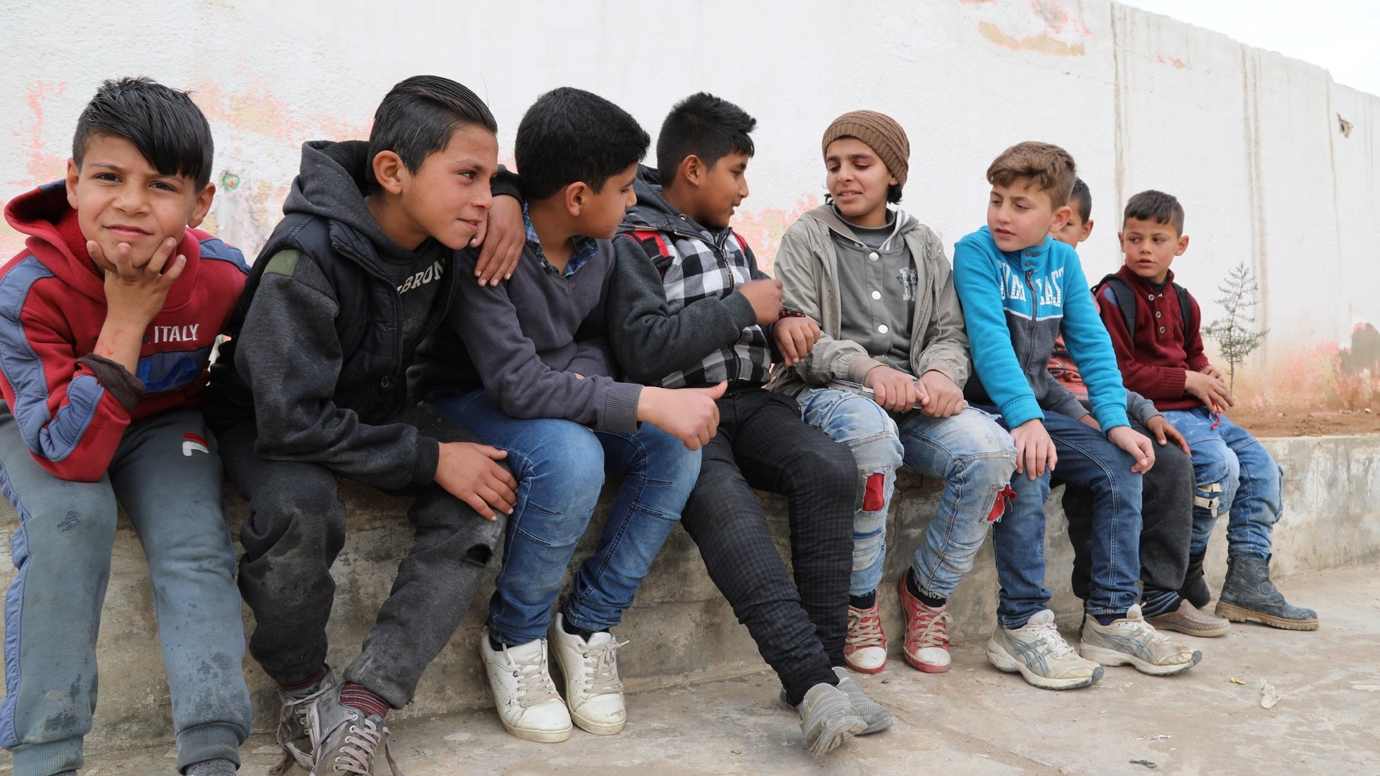 epa07493223 Omar (C), a nine-year-old boy who lost his right leg in a mine explosion, sits with is friends at his school in Raqqa city, northeastern Syria, 01 April 2019 (issued 09 April 2019). The battle of liberation Raqqa from the control of the so-called Islamic State (IS or ISIL or Daesh) group has left at least 1,130 civilians have been killed and another 3,000 people wounded, human rights organizations said.  EPA/AHMED MARDNLI