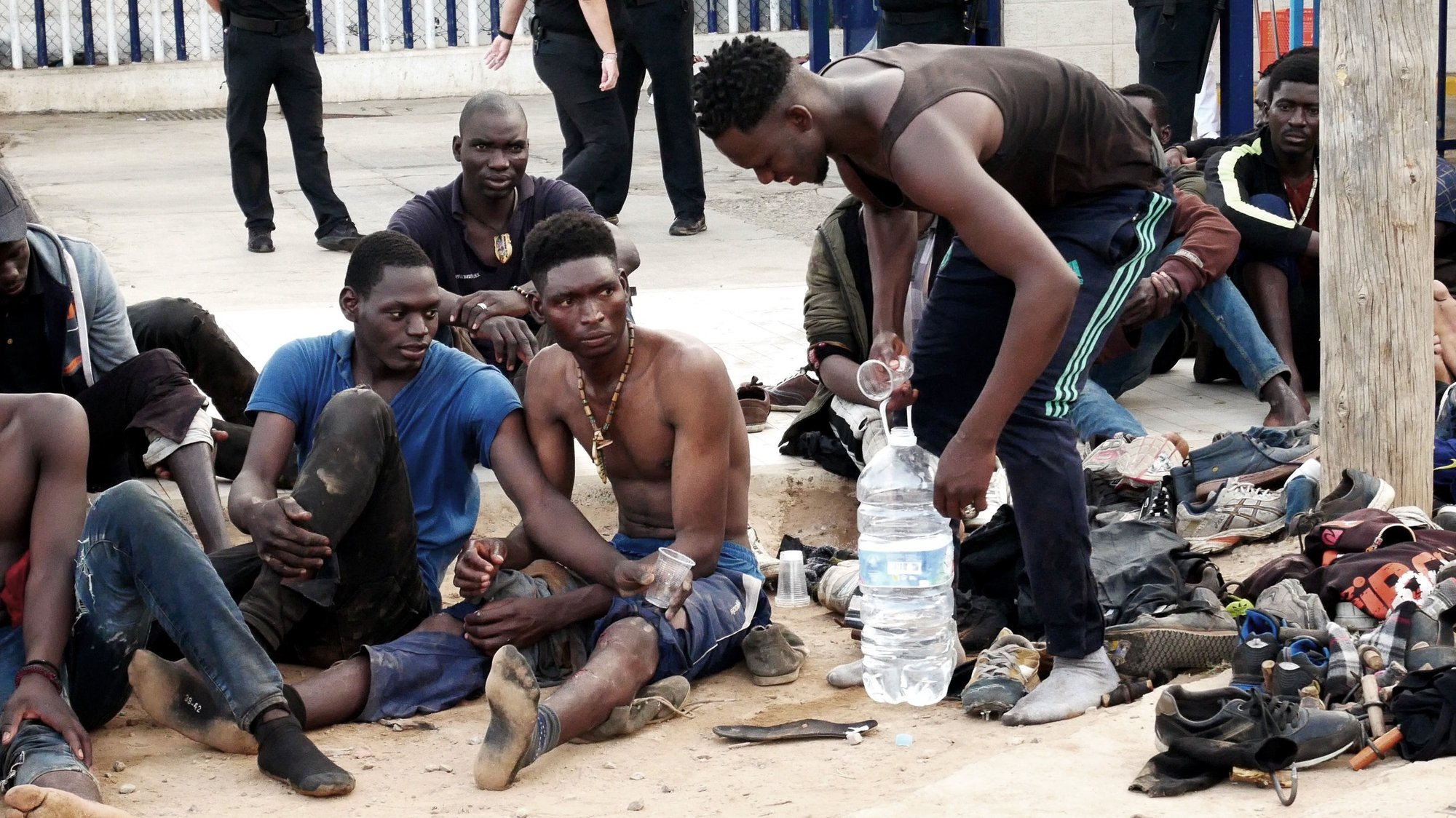 epa09357669 Some migrants rest after they managed to reach Spain by jumping the border fence with Morocco, in Melilla, a Spanish enclave in northern Africa, 22 July 2021. Some 300 migrants managed to reach Spain after they massively jumped the border fence in the early morning.  EPA/PAQUI SANCHEZ