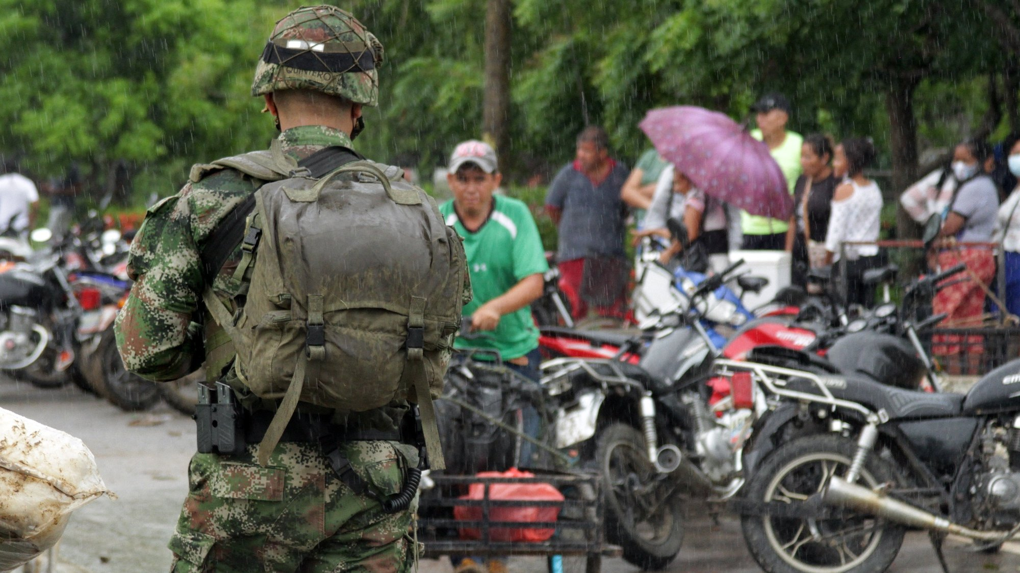 epa09100136 A soldier watches the crossing of Venezuelan migrants from La Victoria, in Venezuela, to Arauquita, in Colombia, in Arauca, Colombia, 26 March 2021. The number of people who have fled from Venezuela to the Colombian town of Arauquita due to armed clashes between the Bolivarian National Armed Force (FANB) and apparent dissidents of the FARC rose this 25 March to 3,961, according to Colombian authorities.  EPA/Jebrail Mosquera Contreras