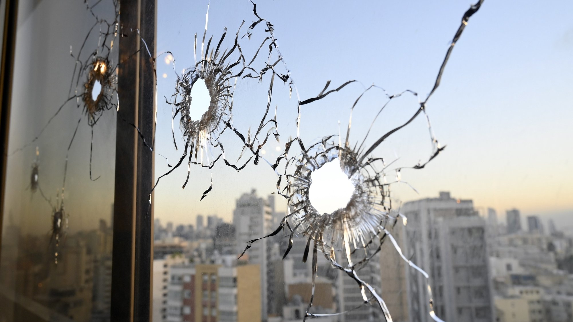 epa09524706 Gun holes are seen on a window at a building a day after clashes in the area of Tayouneh in Beirut, Lebanon, 15 October 2021. At least six people were killed and 20 wounded at a Beirut rally organized by Hezbollah and Amal movements to demand the dismissal of the Beirut blast lead investigator.  EPA/WAEL HAMZEH