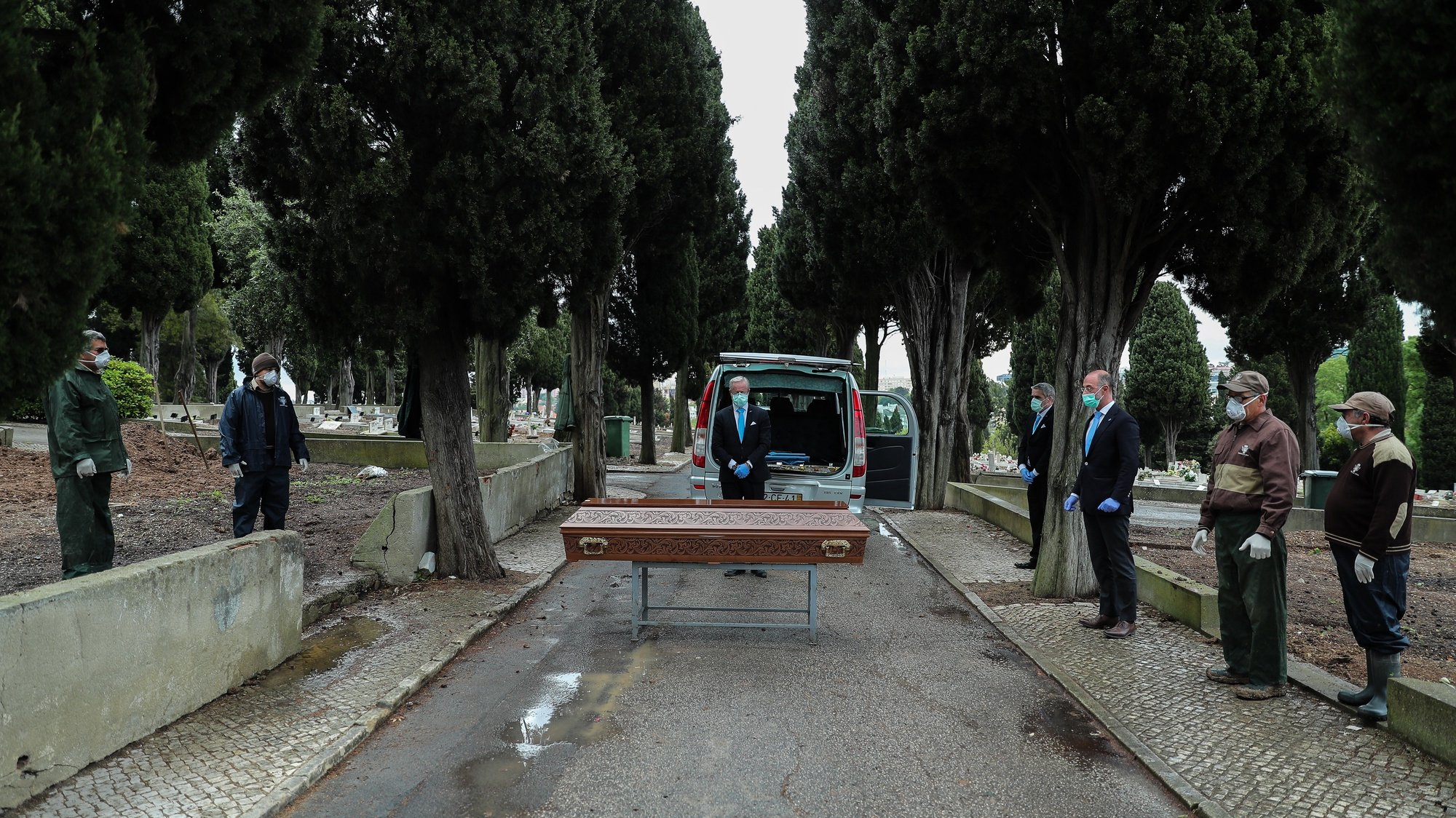 epa08347884 Employees of a funeral home and gravediggers at Benfica cemetery wearing protective masks pay respect to a woman about 30 years old who died of cancer, during the funeral ceremony, in Lisbon, Portugal, 01 April 2020 (Issued 07 April 2020). Portugal is in state of emergency until 17 April 2020. Countries around the world are taking increased measures to stem the widespread of the SARS-CoV-2 coronavirus which causes the Covid-19 disease.  EPA/MIGUEL A. LOPES  ATTENTION: This Image is part of a PHOTO SET