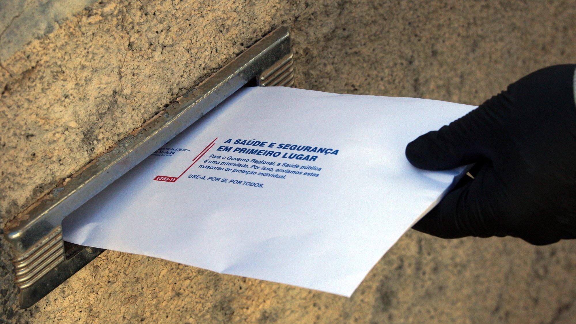 Décio Farinha, carteiro dos CTT Madeira, entrega envelopes enviados pelo Governo Regional contendo máscaras de proteção contra a covid-19, no Funchal, ilha da Madeira, 17 de abril de 2020. HOMEM DE GOUVEIA/LUSA
