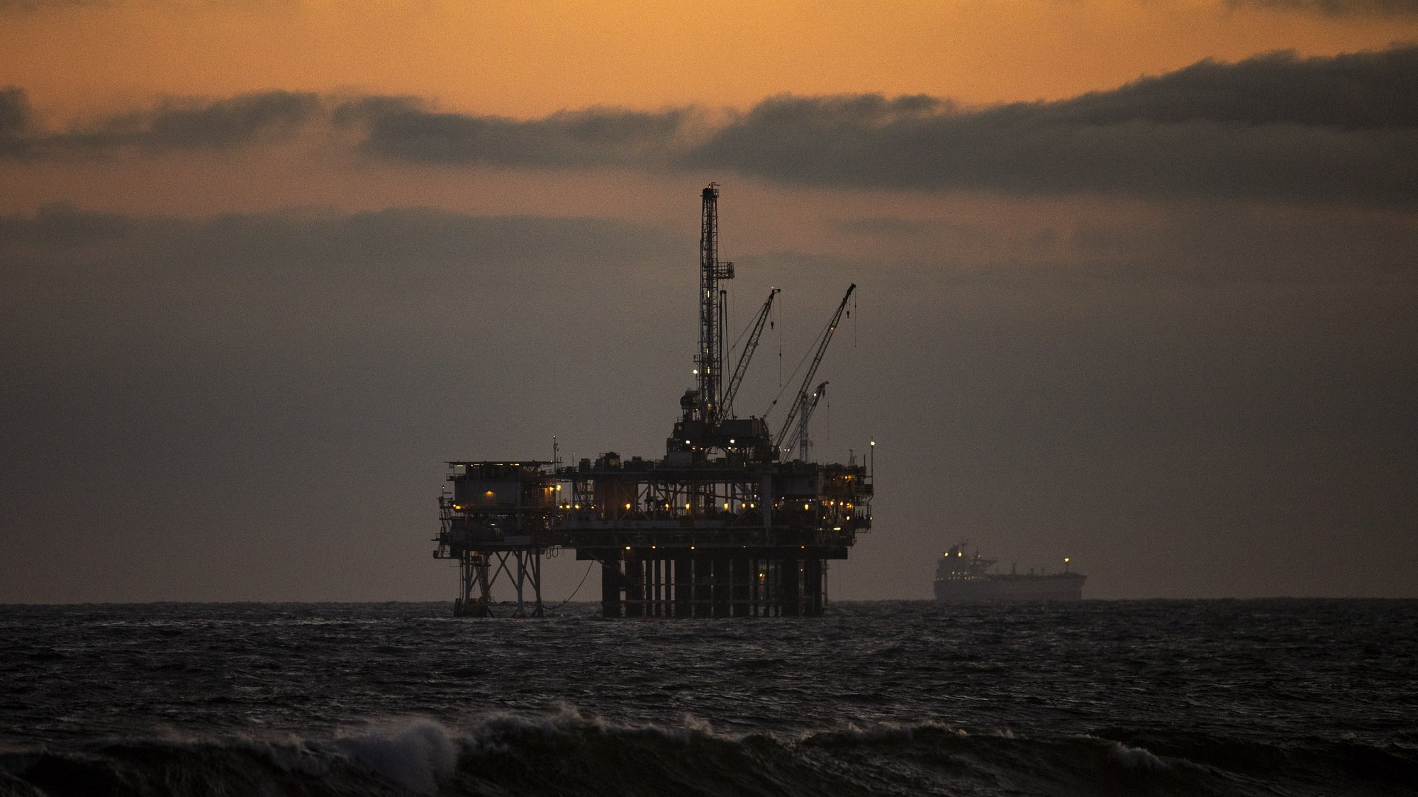 epa08416024 An oil rig sits off the shore at sunset in Huntington Beach, California, 11 May 2020. California begane it's Phase 2 of reopening, after coronavirus restrictions, on 08 May 2020.  EPA/ETIENNE LAURENT