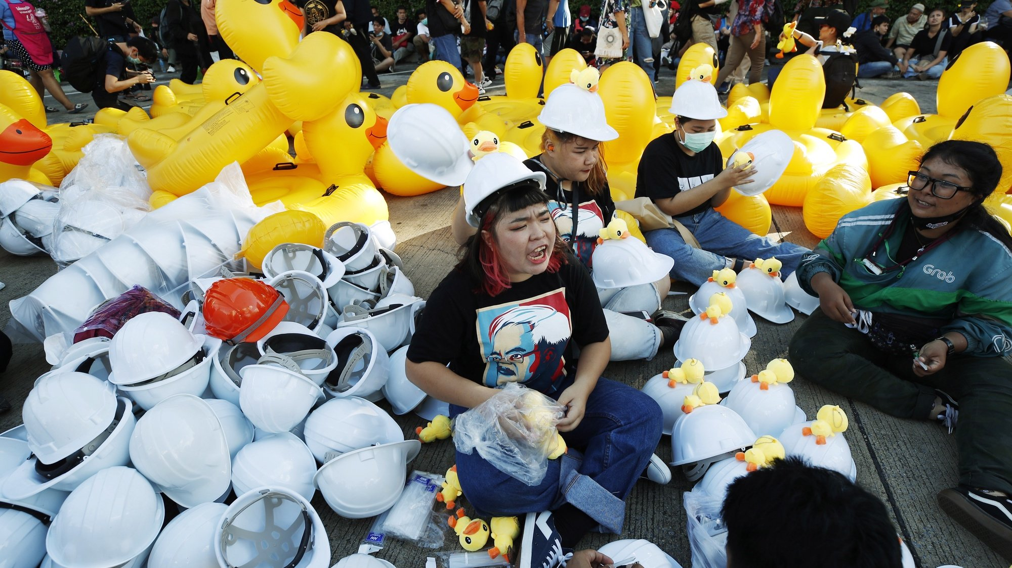 epaselect epa08840410 Protesters glue rubber ducks onto helmets to be distributed to other protesters ahead of an anti-government protest calling for monarchy reform at the Siam Commercial Bank headquarters in Bangkok, Thailand, 25 November 2020. Pro-democracy protesters held a mass rally calling for the monarchy reform and to demand public oversight of the king's assets at the Siam Commercial Bank where Thai King Maha Vajiralongkorn is a major shareholder of the bank.  EPA/DIEGO AZUBEL