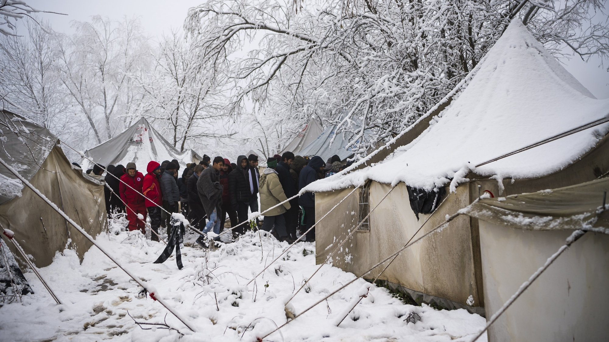 epa08041075 Migrants stand outside from tent during a winter day covered by snow at the Vucjak refugee camp outside Bihac, northwestern Bosnia and Herzegovina, 03 December 2019. According to local media, hundreds of people remain at the camp even after International officials called for it to be shut down.  EPA/JEAN-CHRISTOPHE BOTT