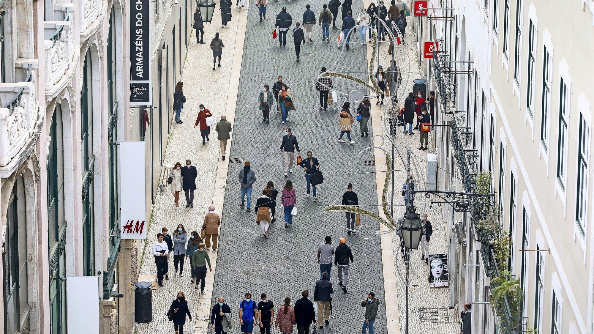 """Cidadãos fazem as suas compras de Natal na Rua do Carmo, antes do recolher obrigatório do estado de emergência, no âmbito das medidas de contenção da covid-19, em Lisboa, 19 de dezembro de 2020. No fim-de-semana os estabelecimentos comerciais apenas podem funcionar entre as 08:00 e as 13:00 nos concelhos classificados como de risco """"extremamente elevado"""" e """"muito elevado"""", medida imposta pelo estado de emergência que estará em vigor até às 23:59 de 23 de dezembro. ANTÓNIO PEDRO SANTOS/LUSA"""