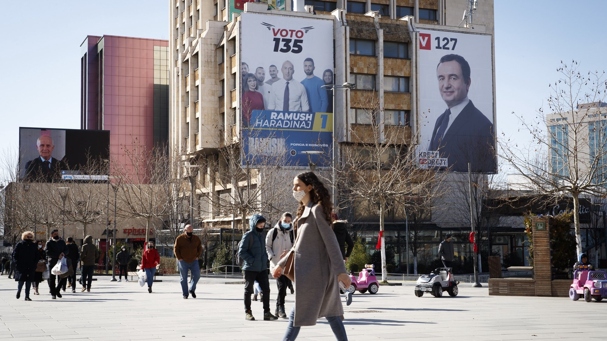 epa09006789 Pedestrians walk in front of the giant electoral posters showing the leader of the movement Self-determination (Vetevendoje) Albin Kurti (R) and leader of the Alliance for the Future of Kosova (AAK) Ramush Haradinaj (L) in Pristina, Kosovo, 12 February 2021. Kosovo's early parliamentary elections will be held on 14 February 2021.  EPA/VALDRIN XHEMAJ
