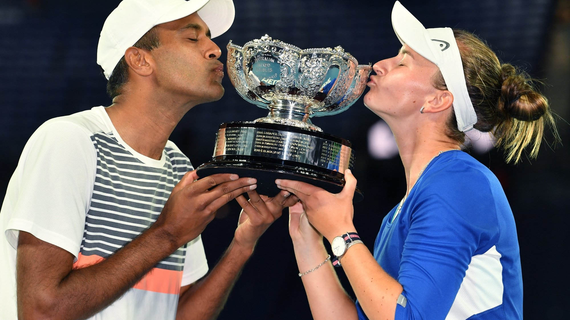 epa09025643 Barbora Krejcikova of the Czech Republic and Rajeev Ram of the United States kiss the trophy after winning the mixed doubles final against Matthew Ebden and Samantha Stosur of Australia on day 13 of the Australian Open tennis tournament at Rod Laver Arena in Melbourne, Australia, 20 February 2021.  EPA/DEAN LEWINS  AUSTRALIA AND NEW ZEALAND OUT