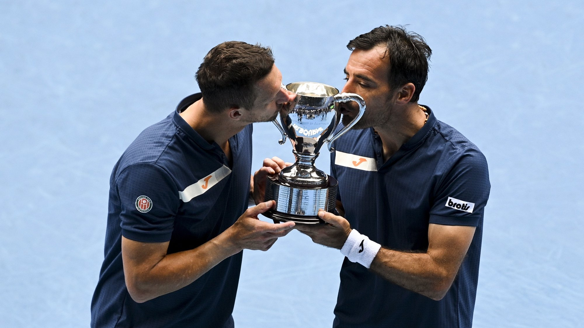 epa09027092 Filip Polasek (L) of Slovakia and Ivan Dodig (R) of Croatia kiss the winners trophy after winning their men's doubles finals match against Rajeev Ram of the USA and Joe Salisbury of Britain at the Australian Open grand slam tennis tournament at Melbourne Park in Melbourne, Australia, 21 February 2021.  EPA/DEAN LEWINS  AUSTRALIA AND NEW ZEALAND OUT