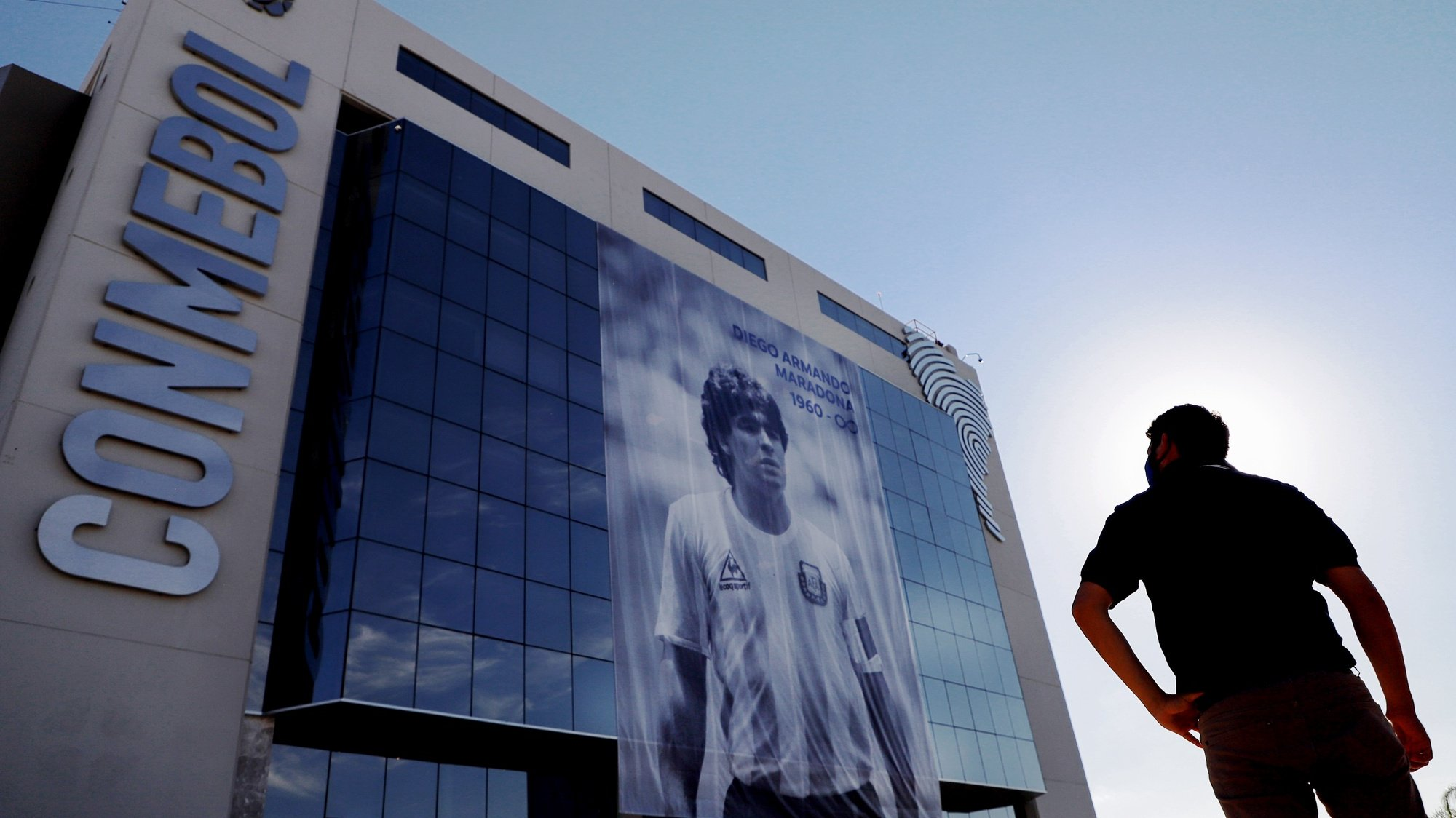 epaselect epa08847393 A man observes a giant banner with a photograph of former Argentine soccer player Diego Armando Maradona, as a tribute, on the facade of the South American Football Confederation (CONMEBOL) building, in Luque, Paraguay, 27 November 2020.  EPA/Nathalia Aguilar