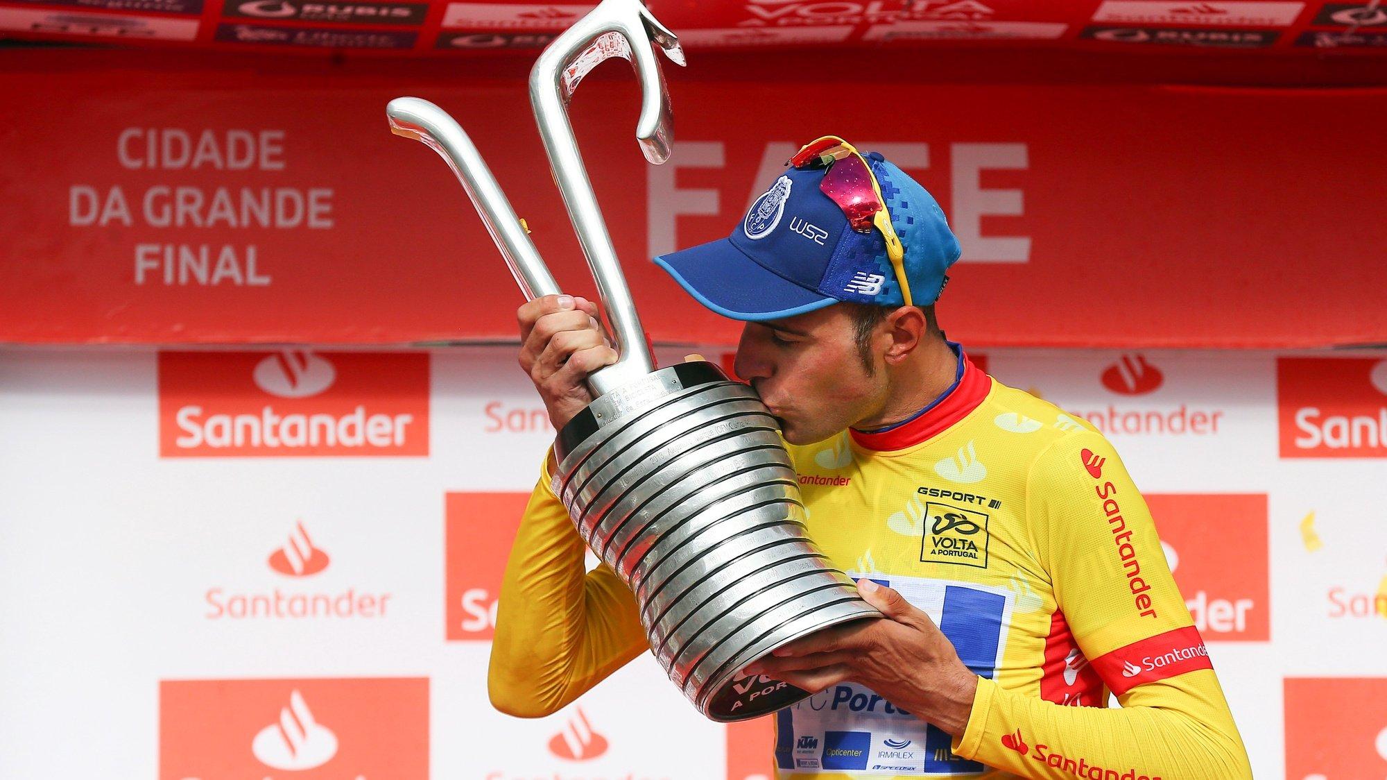 O ciclista Raúl Alarcón, da W52 - FC Porto, beija o troféu de vencedor no pódio, após a 10ª e última etapa da 80ª Volta a Portugal em Bicicleta, um contrarrelógio disputado hoje em Fafe numa distância de 17,3km. Fafe, 12 de agosto de 2018. NUNO VEIGA/LUSA