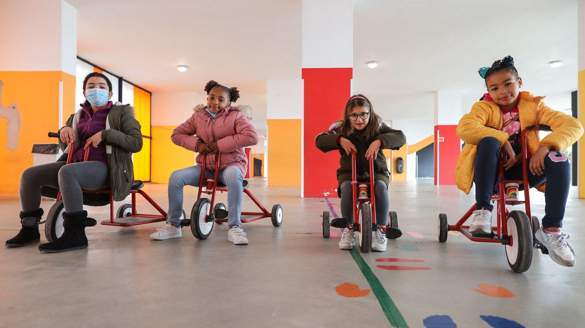 Crianças da Escola EB1/JI de Porto Salvo brincam com triciclos no pátio interior da instituição de ensino. Oeiras, 26 de janeiro de 2021. A escola está a dar acompanhamento a 10 crianças cujos pais são profissionais de serviços essenciais e onde são distribuídas 24 refeições a alunos com escalão A ou B, (ACOMPANHA TEXTO DA LUSA DO DIA 27 DE JANEIRO DE 2021). MIGUEL A. LOPES/LUSA