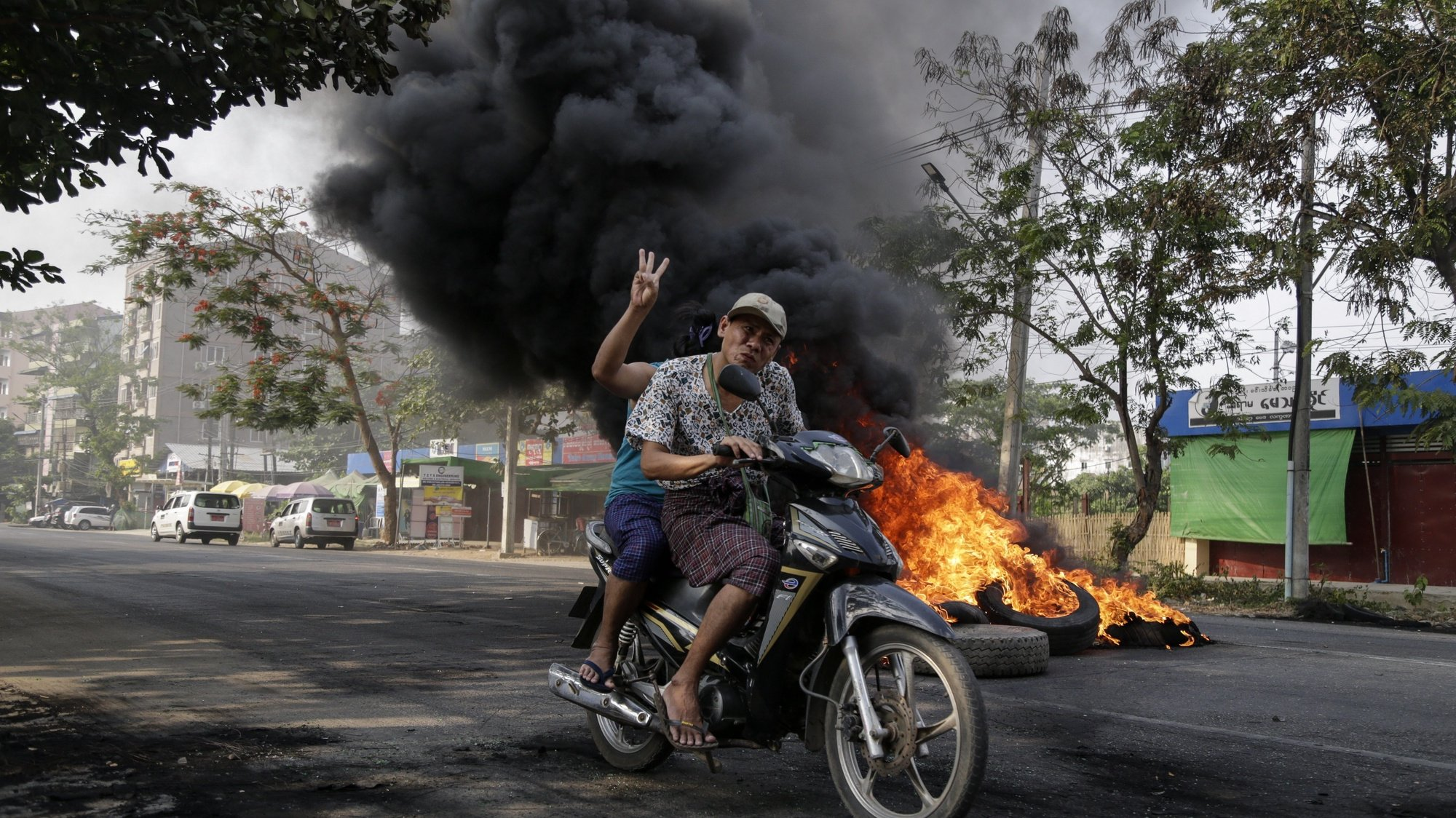 epa09095683 A woman flashes the three-finger salute as as she maneuvers on a motorcycle past burning tires during a protest against the military coup in Yangon, Myanmar, 25 March 2021. Anti-coup protests continued despite the intensifying violent crackdowns on demonstrators by security forces.  EPA/STRINGER
