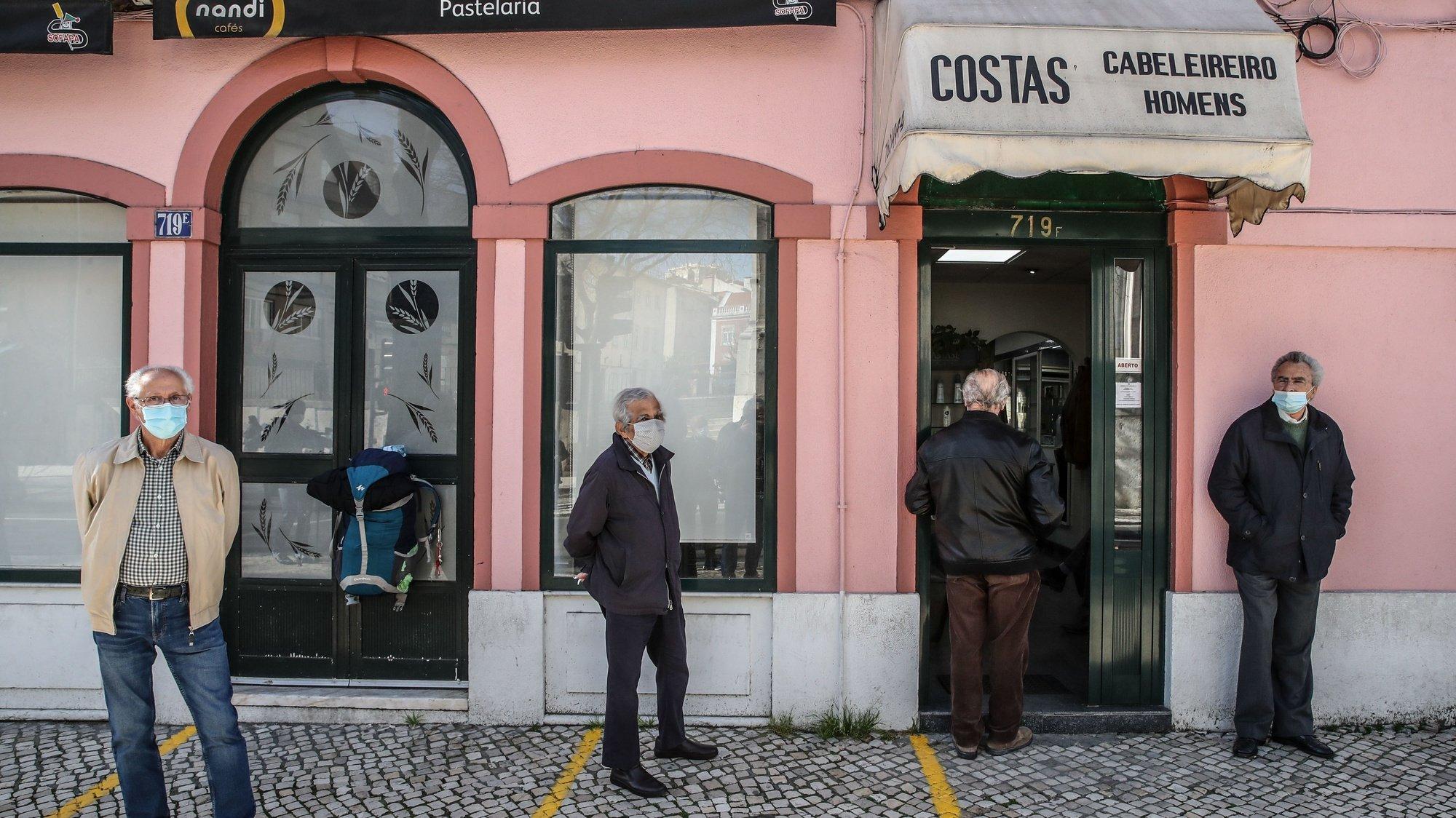 Populares aguardam a vez frente a uma barbearia após a reabertura de comércio não-essencial e cabeleireiros fechado anteriormente após novo decreto do Estado de Emergência devido à covid-19, Lisboa, 15 março 2021.  MANUEL DE ALMEIDA / LUSA