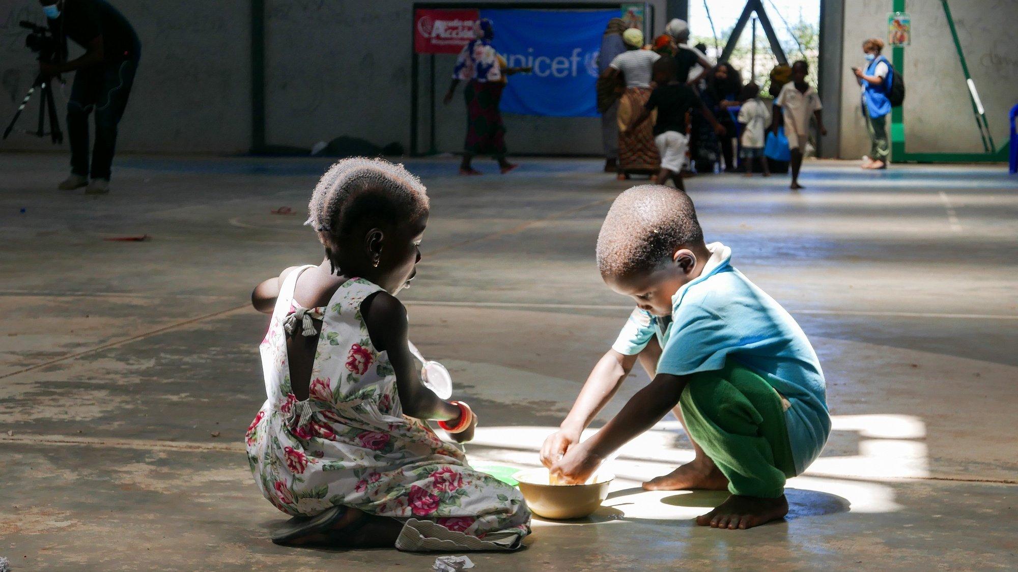 Duas crianças no pavilhão desportivo, no bairro Expansão, em Pemba, alimentam-se com refeições confecionadas por um grupo de mulheres de Pemba, que decidiu fazer hoje para os deslocados do ataque a Palma, em vez de descansar no feriado do Dia da Mulher Moçambicana, Cabo Delgado, Moçambique, 07 de abril de 2021. Os ataques são só uma ponta do problema que se estende desde as zonas de conflito até Pemba e outras cidades, seguras, mas agora sobrelotadas com a vaga de 700.000 deslocados em três anos e meio de conflito. (ACOMPANHA TEXTO). LUÍS MIGUEL FONSECA/LUSA